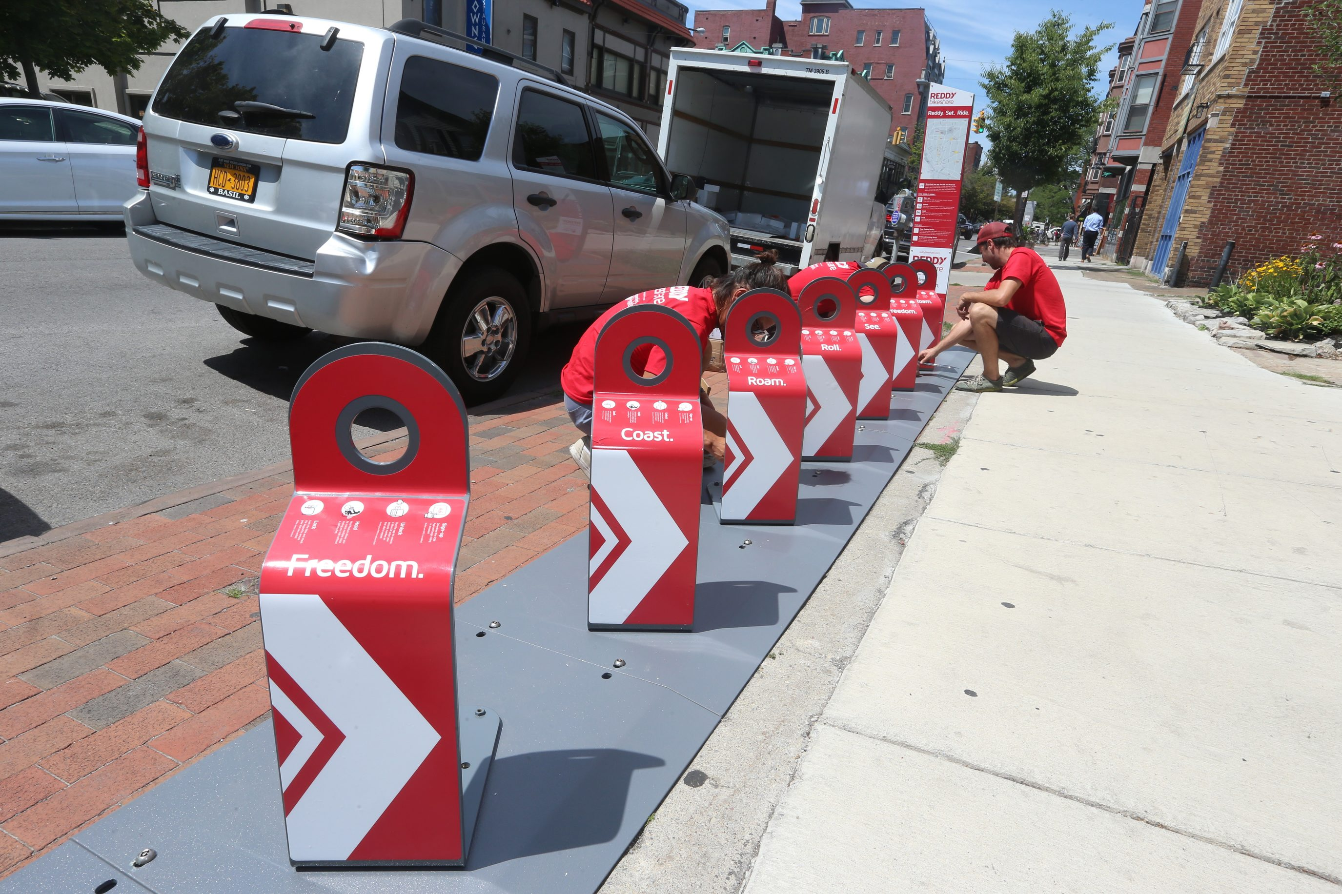 Workers from REDDY Bikeshare install a station on  Allen Street in Buffalo on July 20.  (John Hickey/Buffalo News)