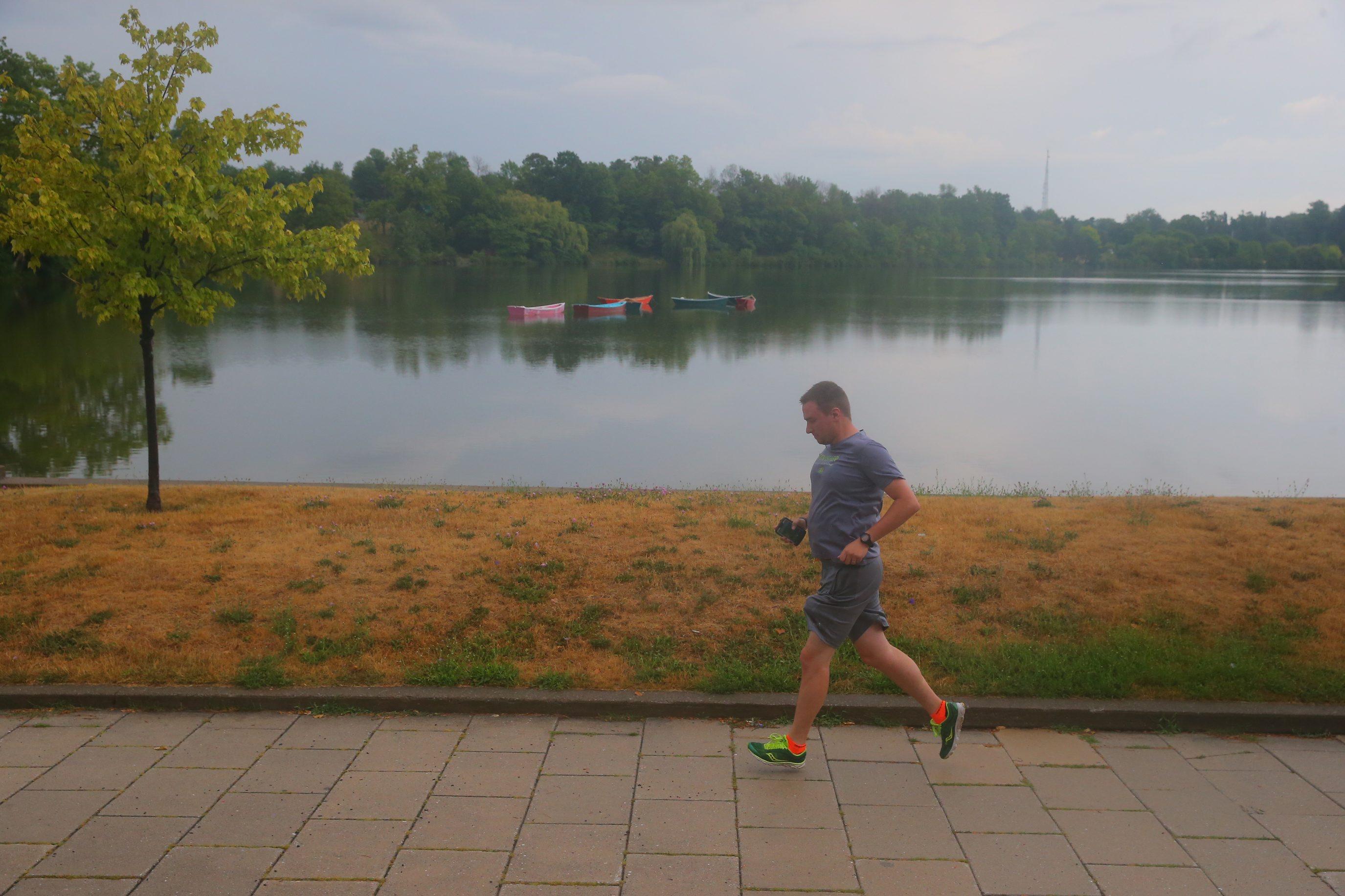 A jogger runs by Hoyt Lake at Delaware Park as a light rain falls in Buffalo on Monday.  (John Hickey/Buffalo News)