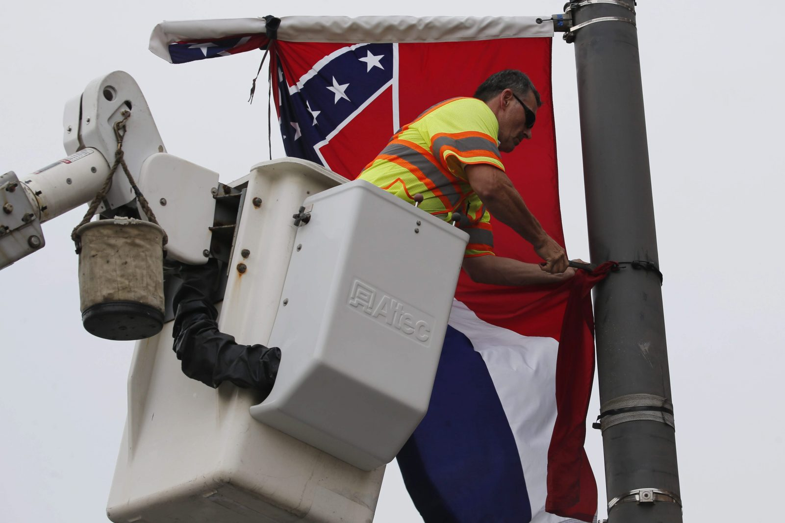 A city worker removes the Mississippi flag from a public light stand after a standoff with protesters on Broad Street in Philadelphia, Monday, July 25, 2016. (Photo by Derek Gee)