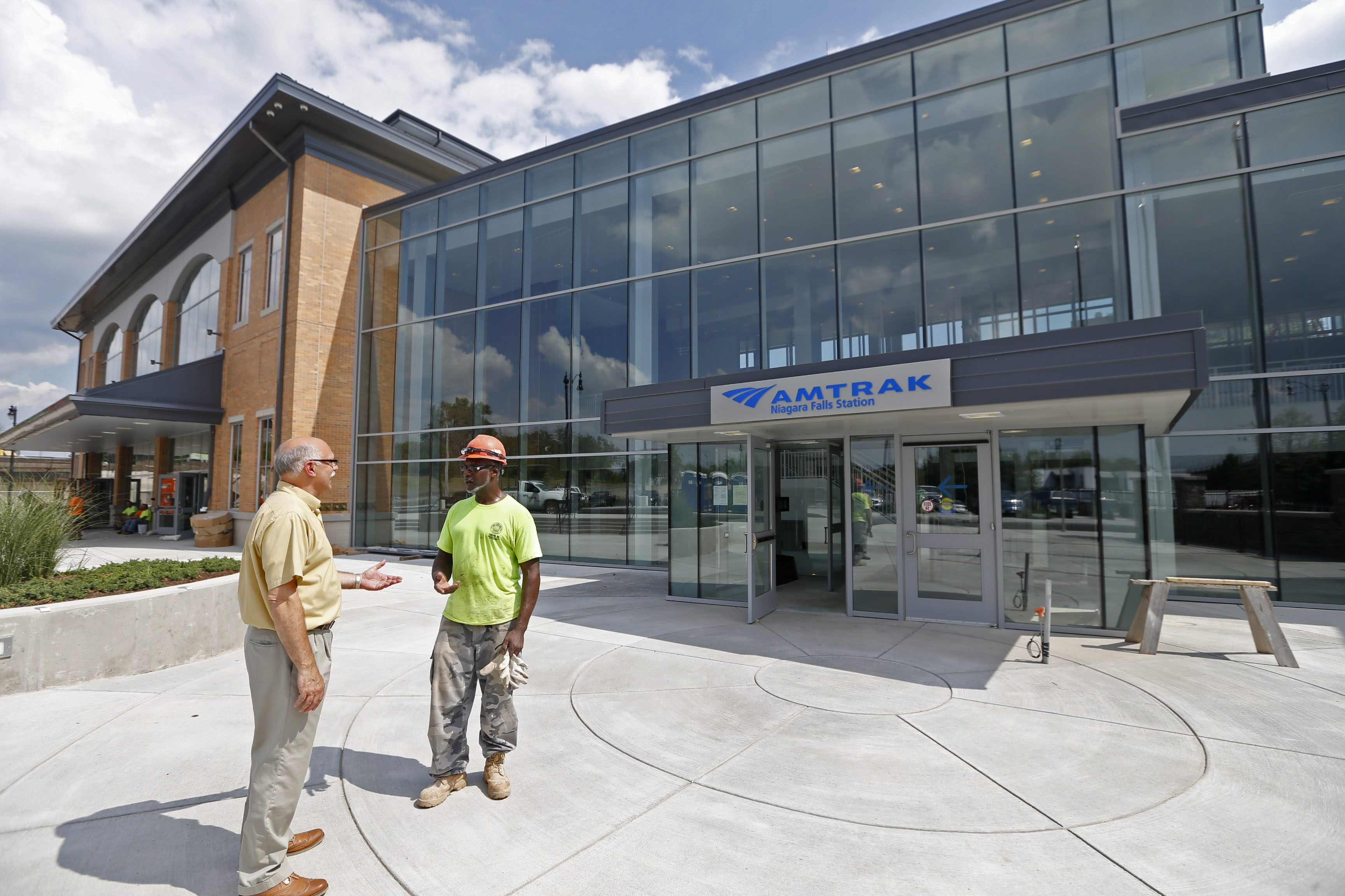 Clyde Coleman, a union laborer with Scrufari Construction, right, visits with Thomas DeSantis, acting director of planning and economics for the City of Niagara Falls, near the main entrance of the new $43 million Amtrak train station in Niagara Falls. (Robert Kirkham/Buffalo News)