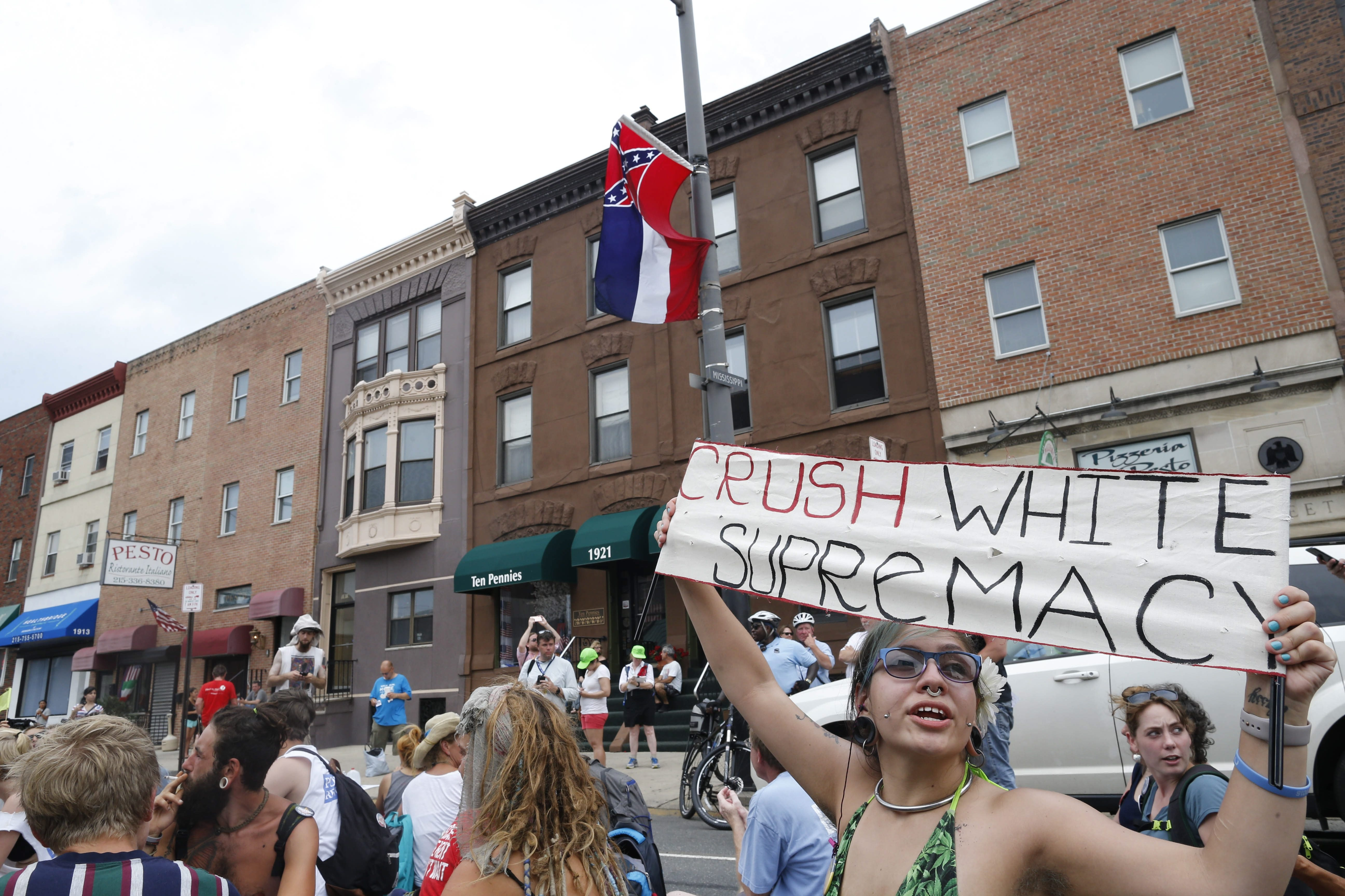 "Upset by how the Democratic Party treats them and their candidate, backers of Sen. Bernie Sanders rally around a cause on Broad Street in Philadelphia: With help from a city bucket lift, they got a state flag of Mississippi – and its Confederate symbol – removed from a lamp post. One demonstrator called it ""a moment of pure elation and pure peace."" (Derek Gee/Buffalo News)"