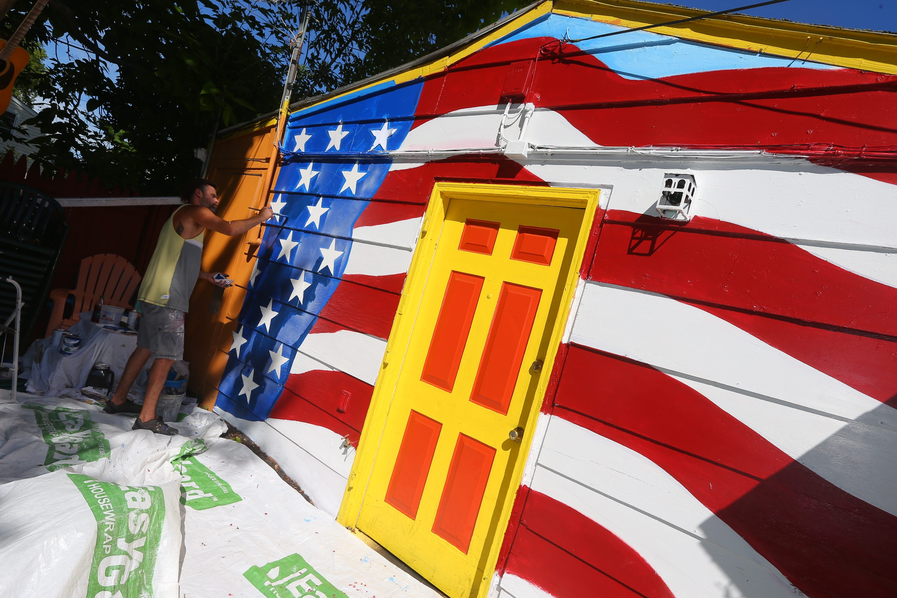 Clarence artist Blair Rusin paints an American flag mural Thursday in the outdoor seating area at Old Man River restaurant in Tonawanda in support of Vietnam Veterans Chapter 77.