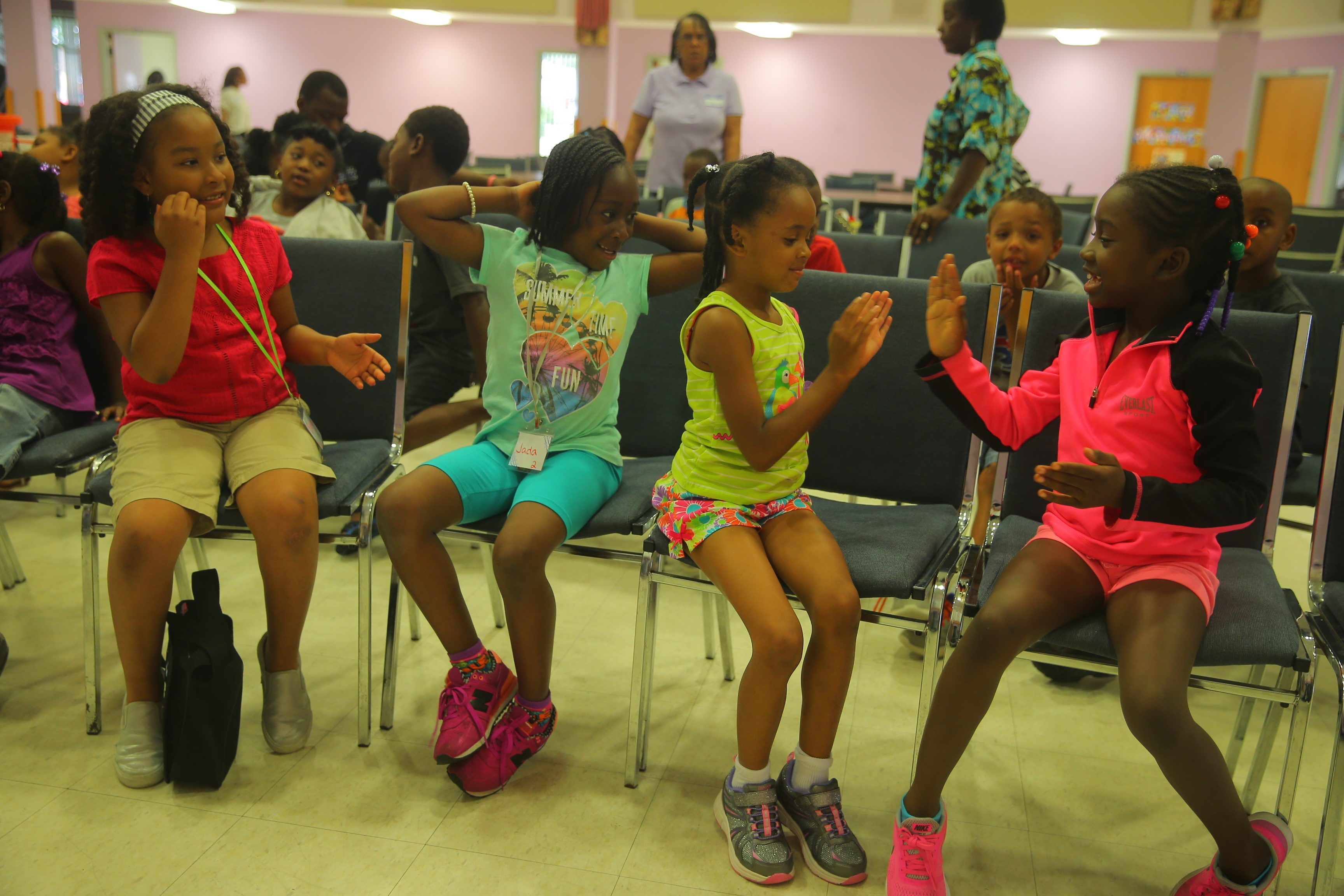 From left, Bethany Callahan, 7, and Jada Knight, 8, look on as Lanija Harrington, 6, and Adrianna Mattison, 7, play patty-cake as they wait for dismissal at the Buffalo Say Yes Summer Camp Program at Mount Olive Baptist Church. (John Hickey/Buffalo News)
