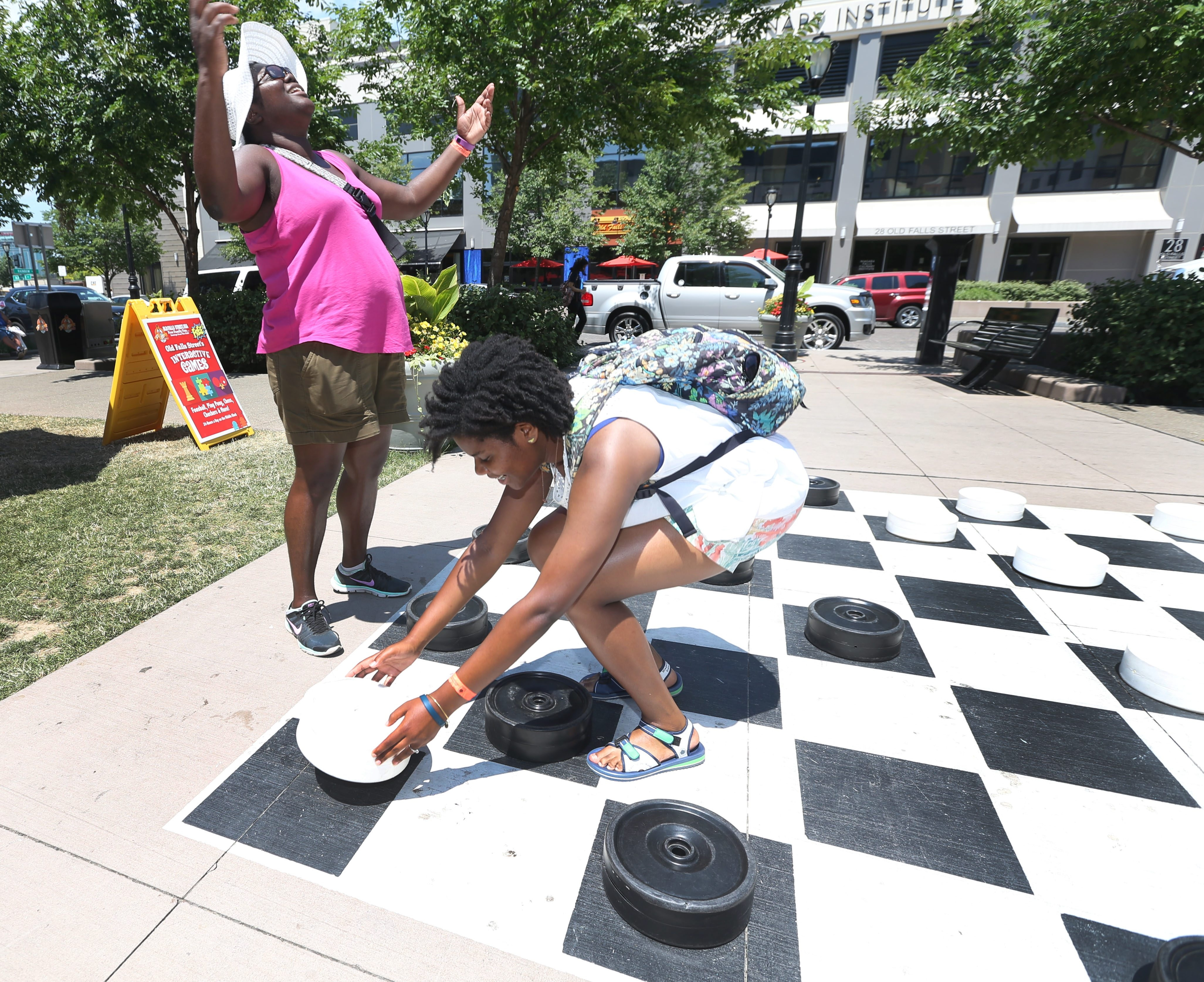 Old Falls Street in Niagara Falls has various activities for the family. The area has various games and Adirondack chairs to relax. Chelsea Presley, pink, of Batesville Mississippi, and her daughter Ciera, 16, play a giant game of checkers, Tuesday, July 5, 2016. The family is in Niagara Falls for vacation.  Ciera gets a double jump. (Sharon Cantillon/Buffalo News)