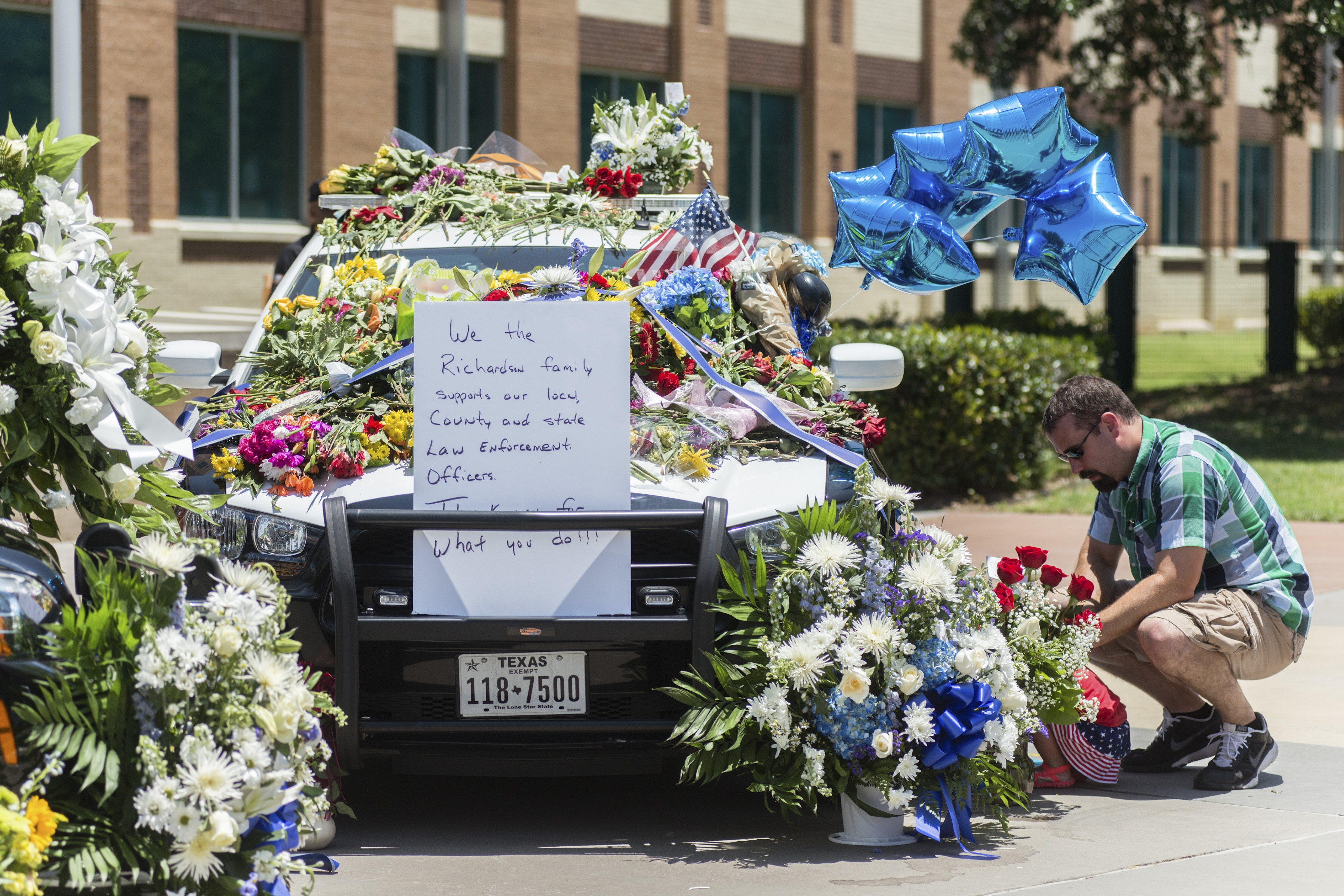 Brandon Stafford pays his respects at a makeshift memorial by a patrol car outside the Dallas Police Department headquarters on Friday, the day after five officers were shot dead. In Buffalo, police shootings are infrequent. Two people have died in armed confrontations and two have been wounded since 2012. (New York Times)
