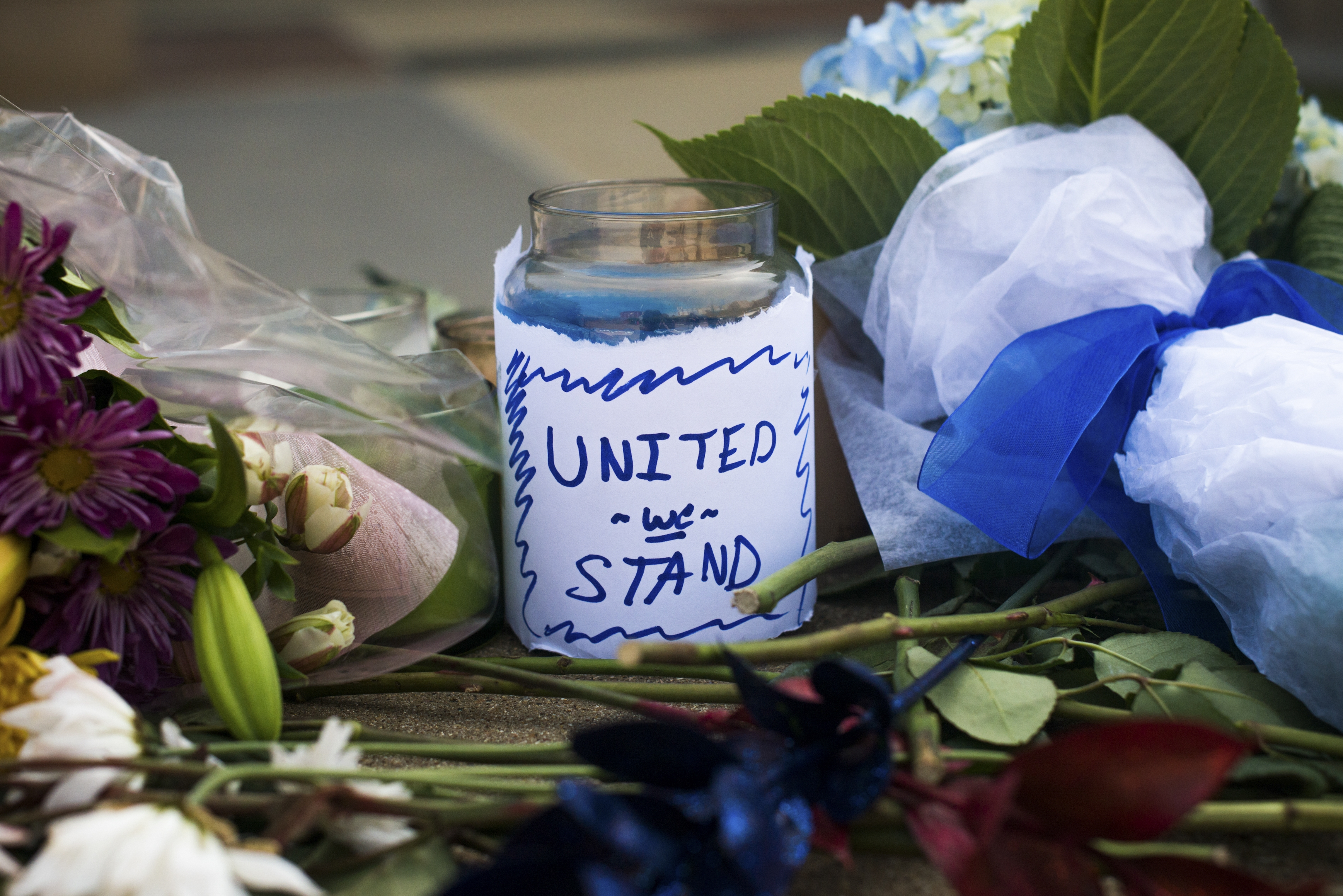 A candle with the message 'United We Stand' sits amongst other mementos at a makeshift memorial set up outside Dallas Police Department headquarters, following a sniper attack that  five officers and wounded seven others at a demonstration on Thursday night against police shootings in Minnesota and Louisiana. (The New York Times)
