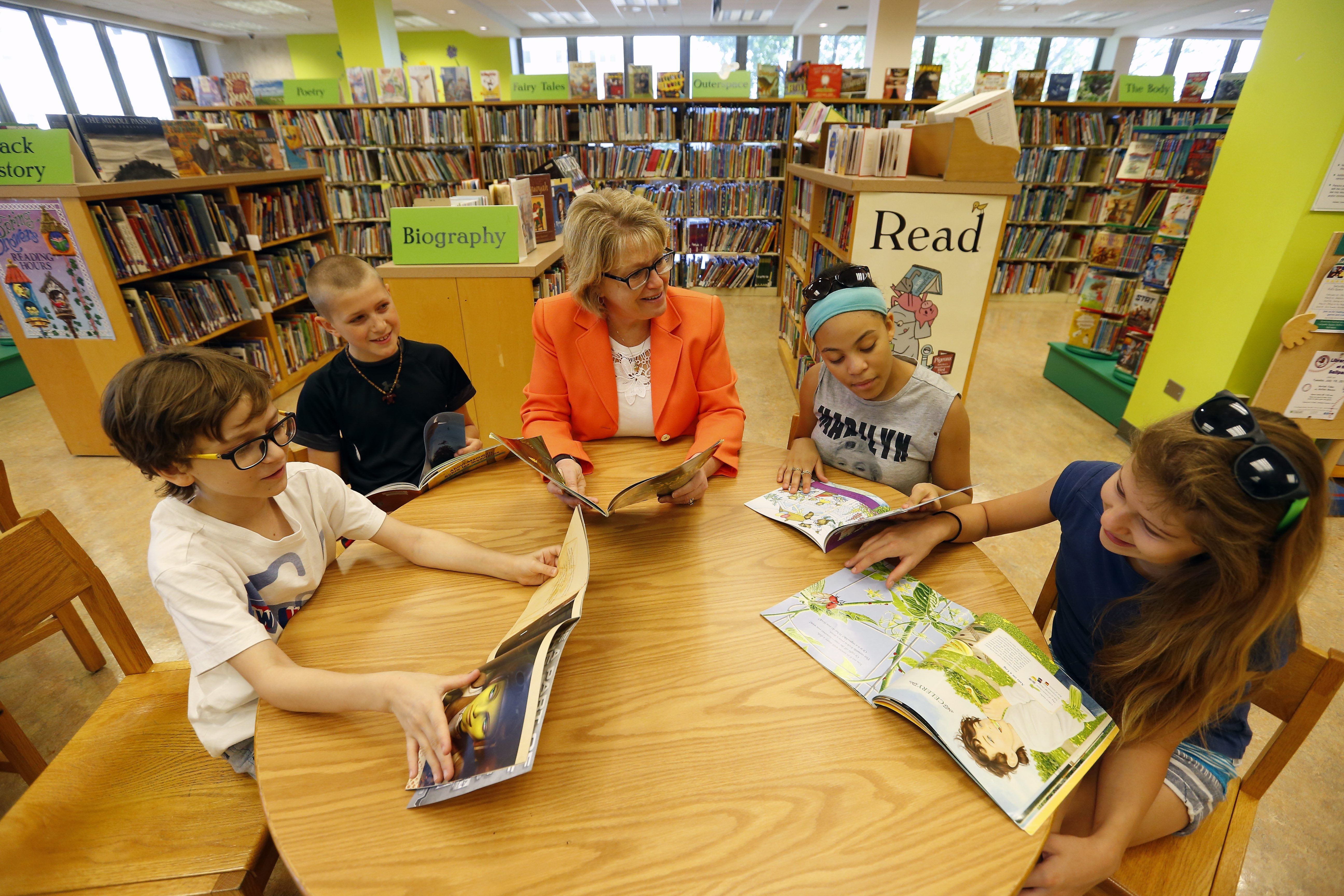 """We encourage children to ... open up their worlds through reading."" – Buffalo & Erie County Public Library System Director Mary Jean Jakubowski, with Elmwood Charter School 6th-graders, from left, Gabe Maddox, Salvatore Teresi III, Marisa Robinson and Gracie Nagy at the Central Library."
