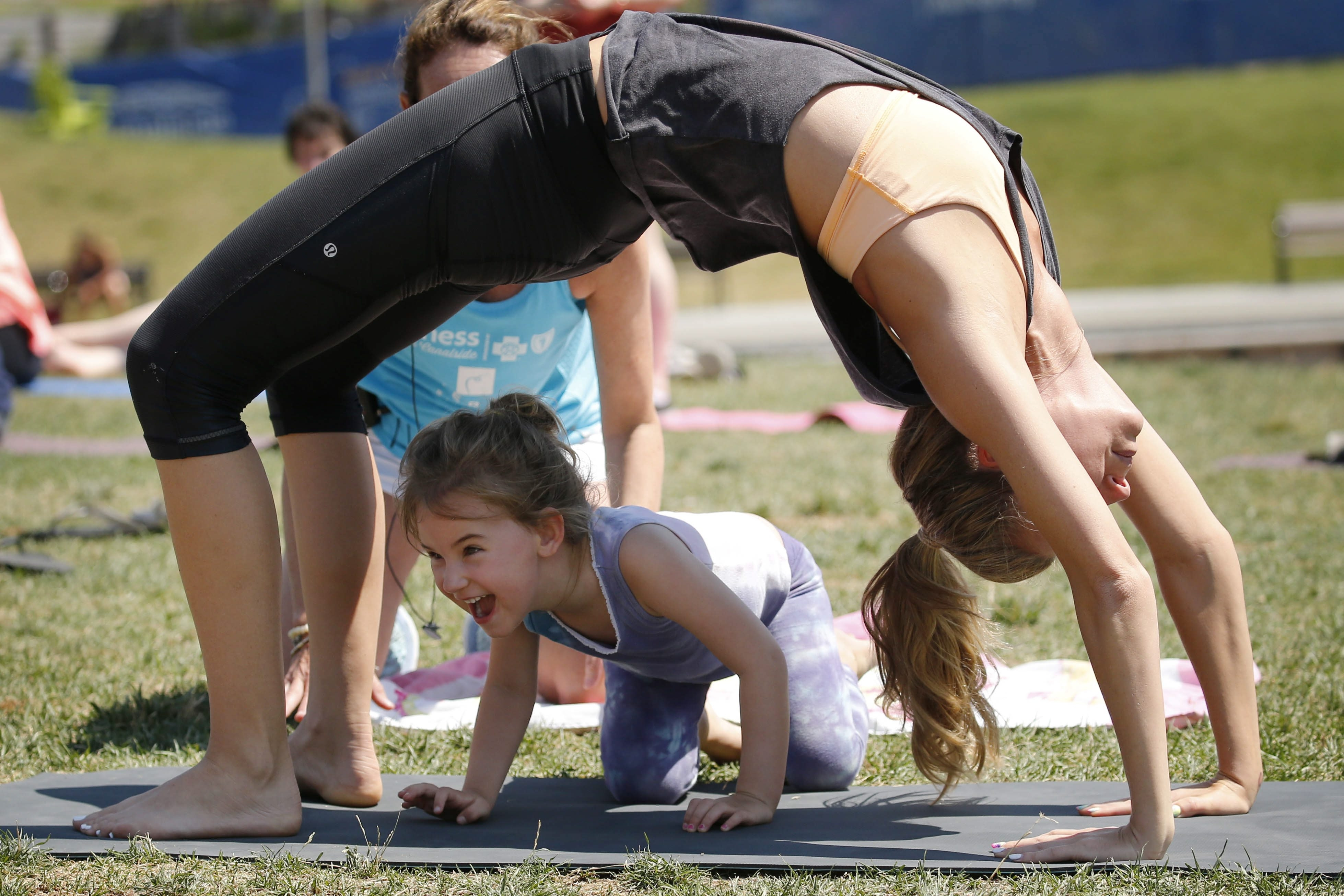 Teresa Falsone does a bridge pose while her daughter Francesca, 4, scampers underneath her to great amusement during a session of Jody Quinn's family yoga class at Canalside. (Derek Gee/Buffalo News)