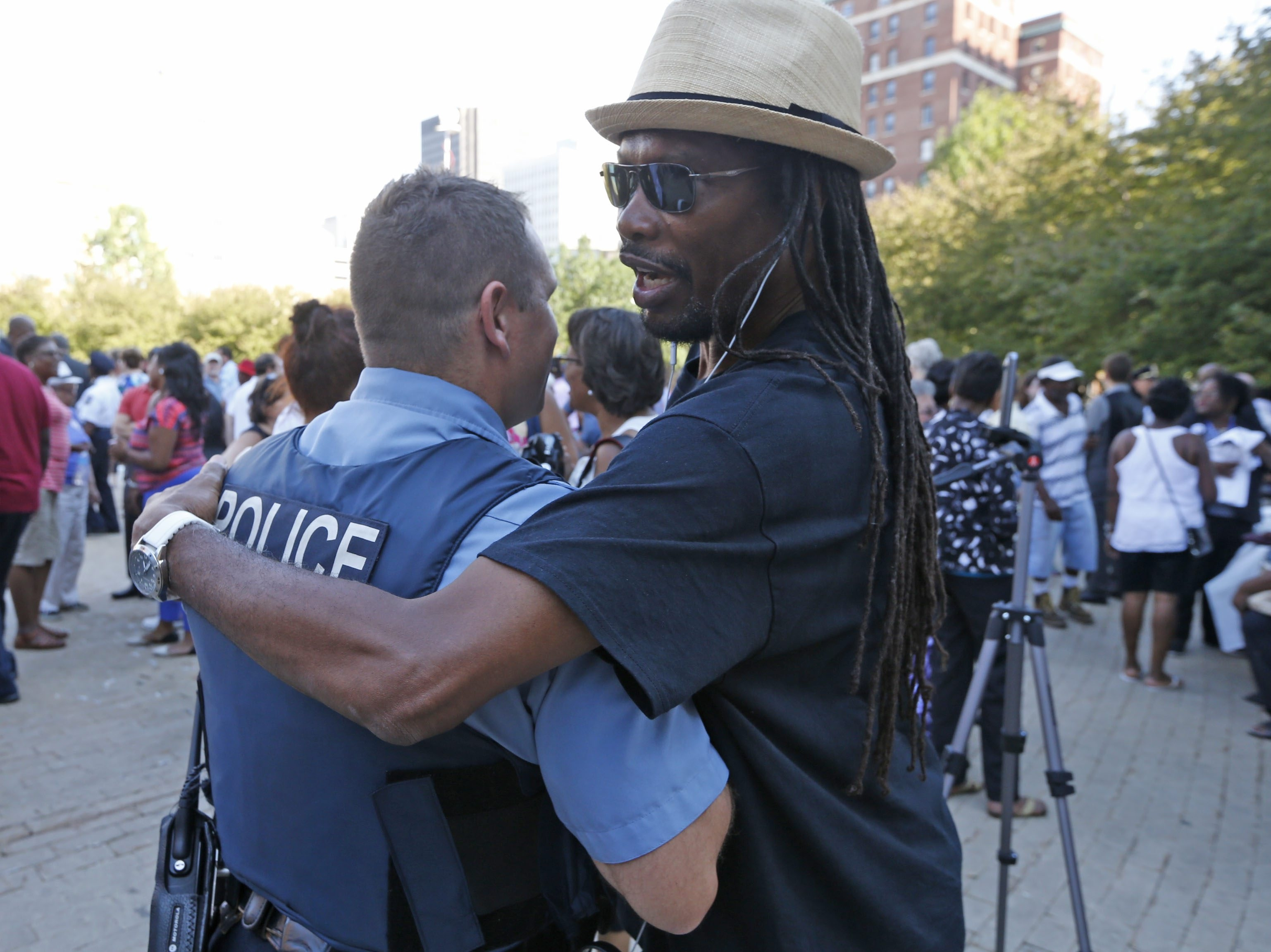 Ron Stewart, a sociology professor at SUNY Buffalo State, right, hugs a former student, Cheektowaga Police Officer Dave Vogel, at the community rally in Niagara Square on Tuesday.