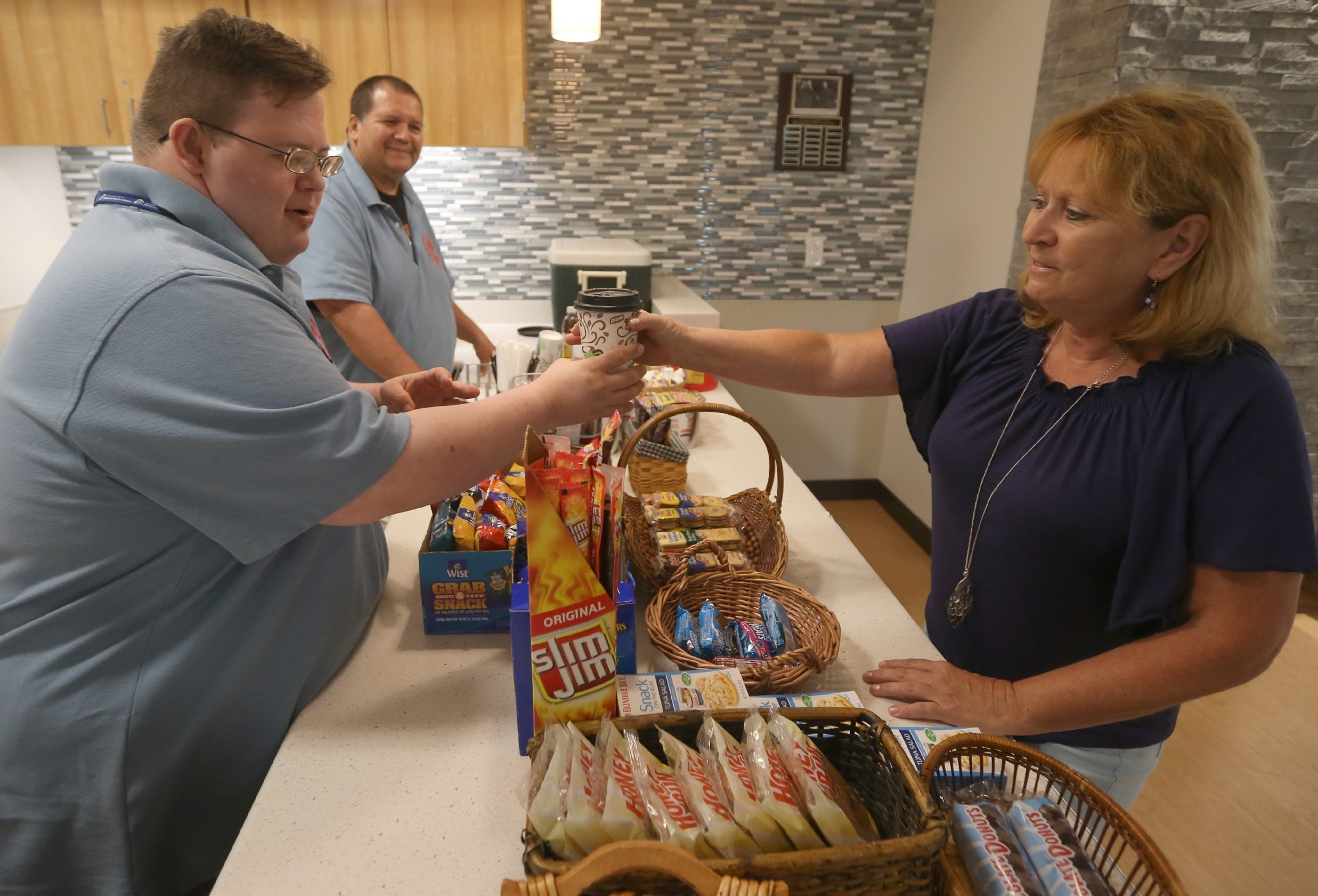 George Augstell sells a coffee to Nancy Secic at his coffee shop in the Golisano Center in Buffalo as his employee and job coach Eddie Chew looks on.  Augstell, who has Down syndrome, opened Uncle Bill's Coffee Stop with help from People Inc.