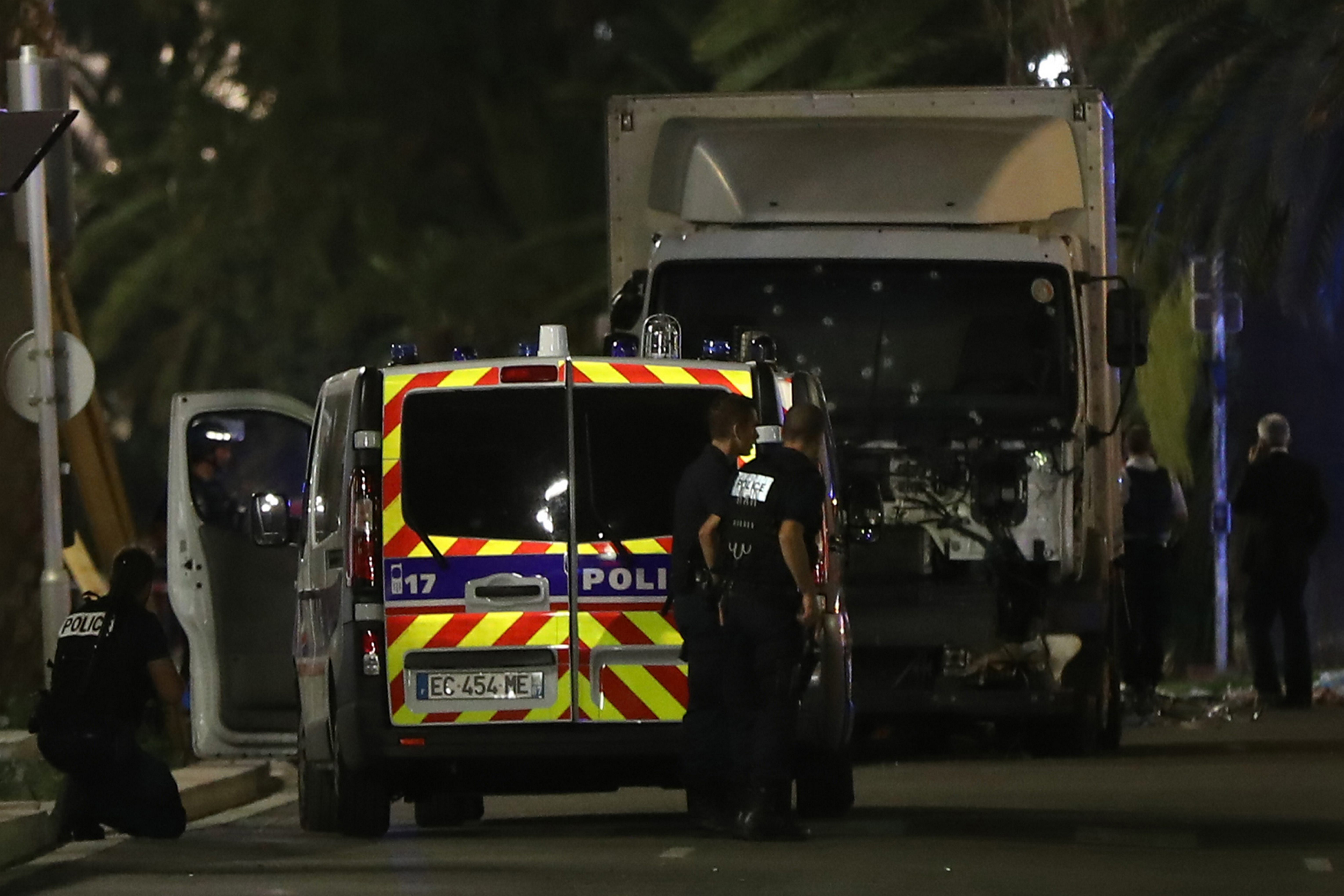 Police officers stand near a truck that drove into a crowd leaving a fireworks display in the French Riviera city of Nice, killing at least 70 people and injuring about 100. The Interior Ministry reported that the driver of the truck was shot.