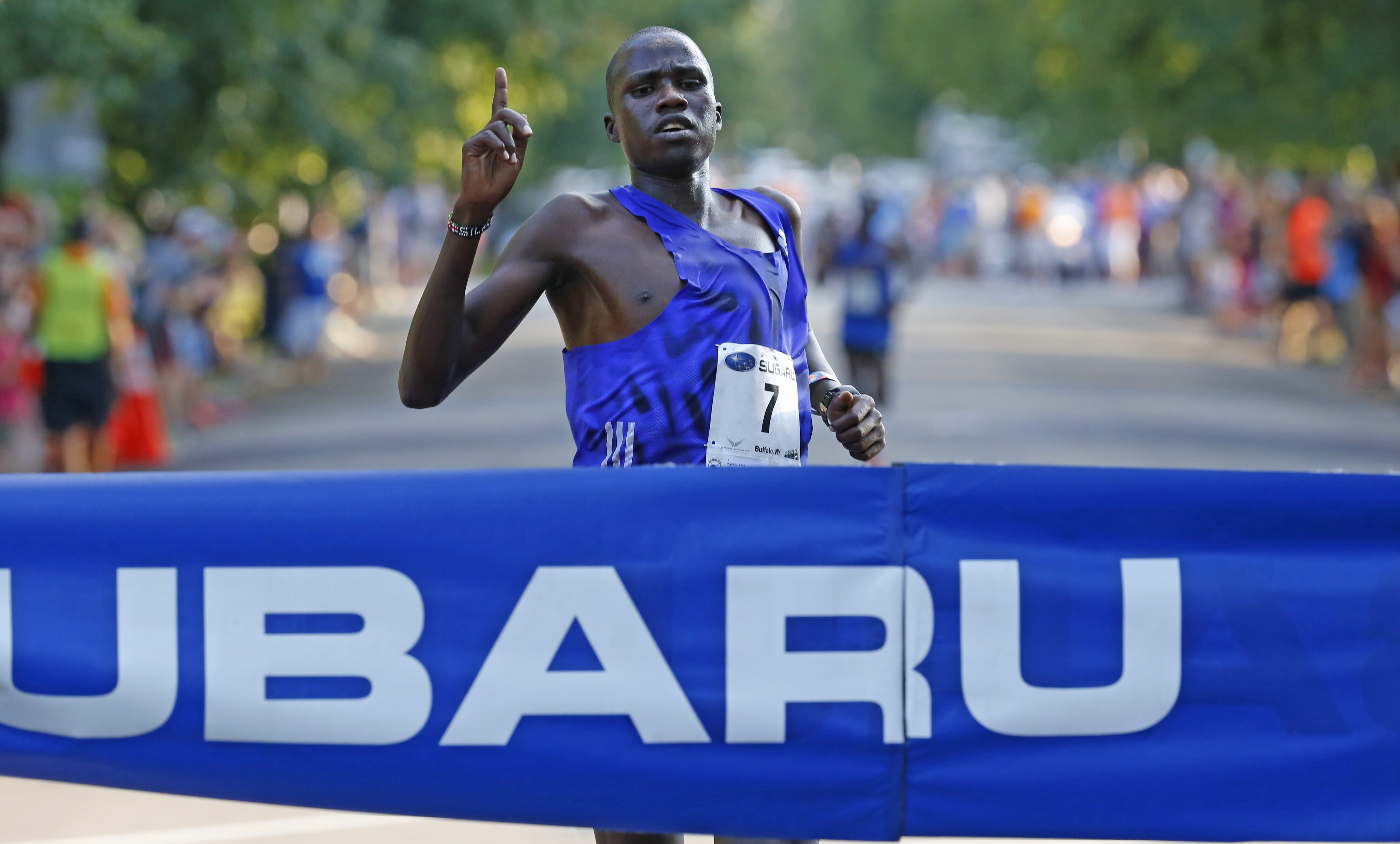 Silos Kipruto hits the finish line first in 18:13 at Friday's Subaru 4 Mile Chase. Kipruto had a 4:26 split for the last mile.