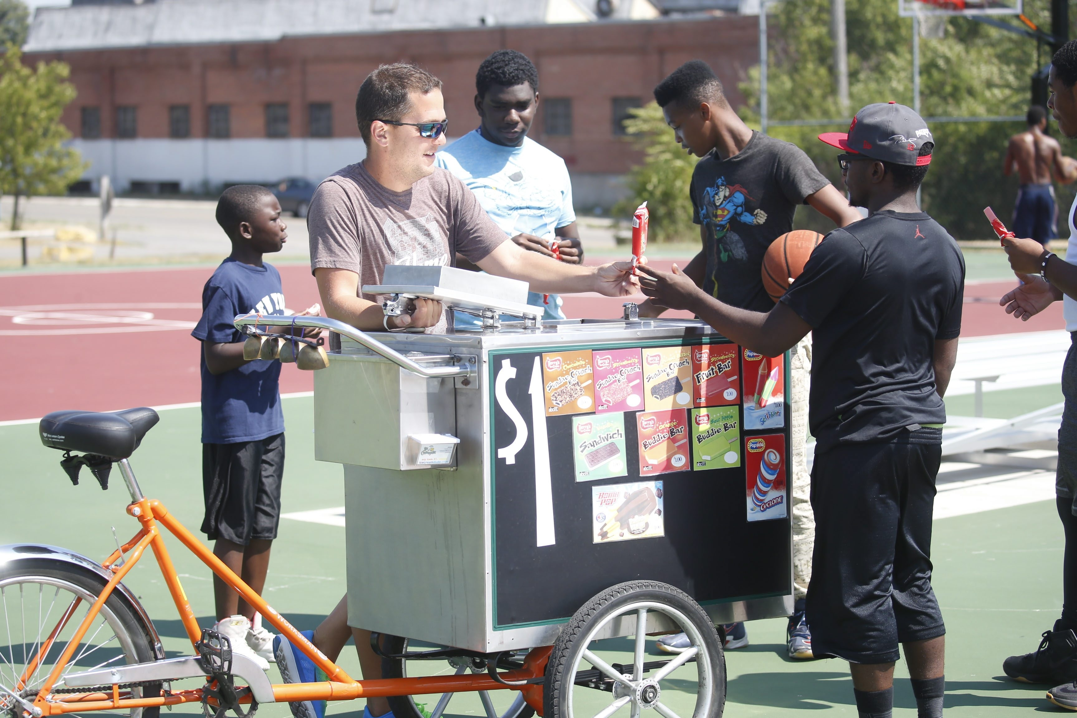 "James Karagiannis, also known as the ""Ice Creamcycle Dude,"" stops to give out ice cream in a park on Buffalo's East Side. Karagiannis owns a fleet of six cycles that comb the city's poorer neighborhoods, selling packaged ice cream for $1. (Robert Kirkham/Buffalo News)"