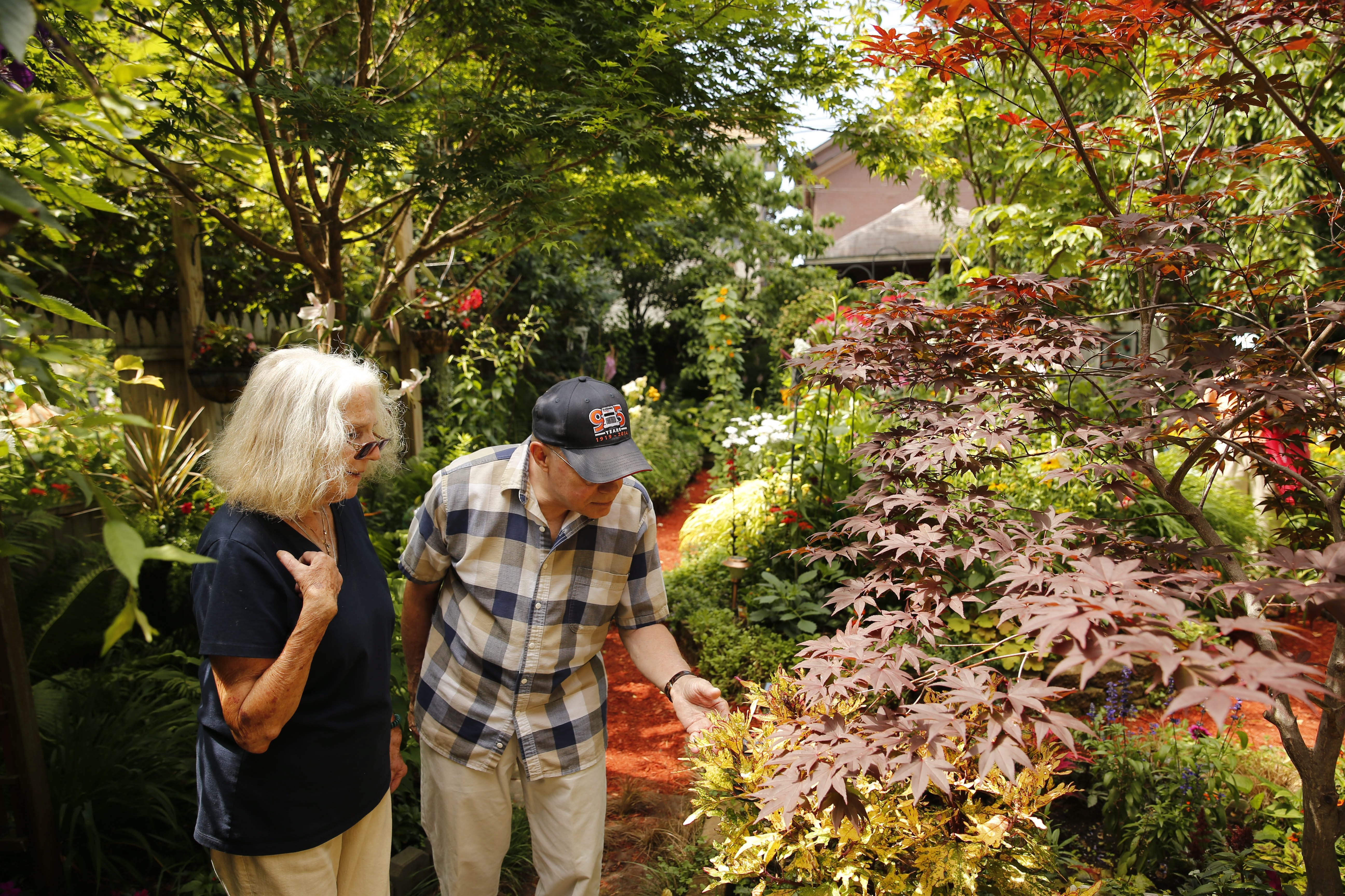 Neighbor Edith Bartlett and David Krellner tour the garden of Jim Ecker on Johnson Park during last year's Garden Walk.  (Derek Gee/Buffalo News)