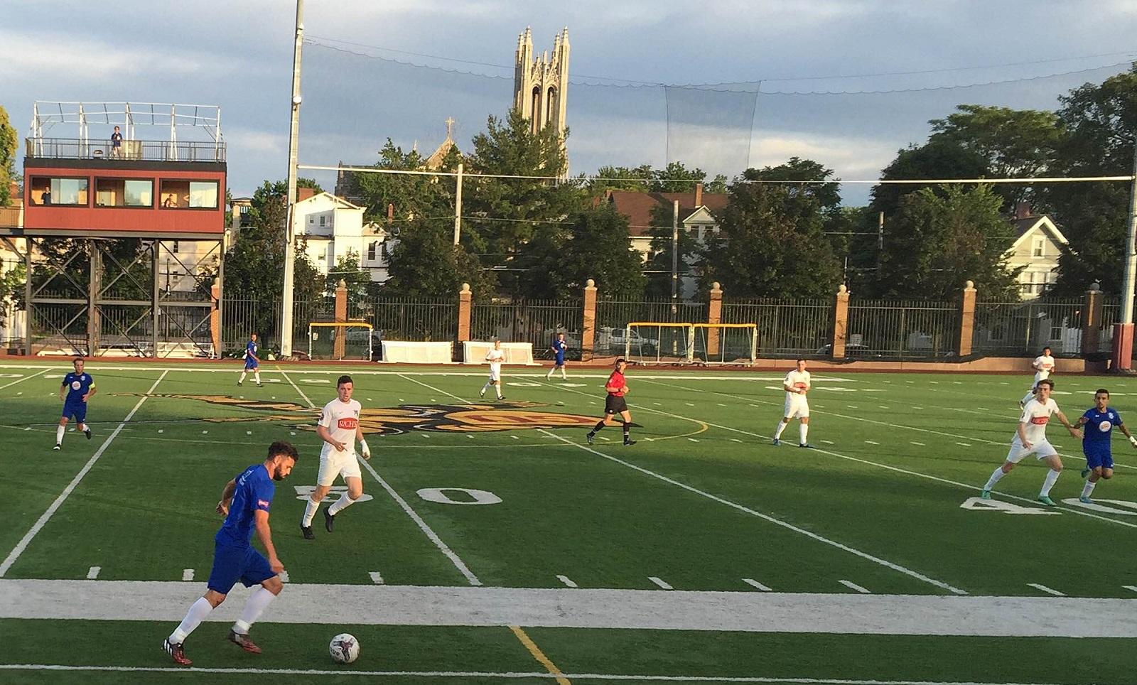 Kieran Toland, in white closest to the ball, watches as Scott Byrum prepares to play a long ball forward. (Ben Tsujimoto/Buffalo News)