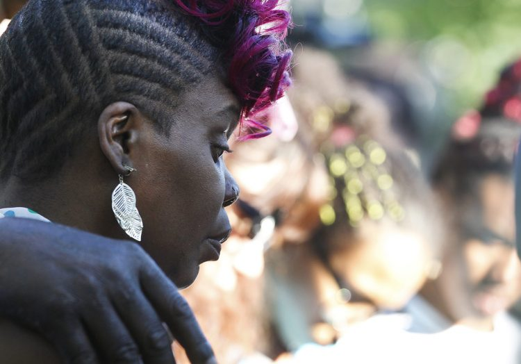 A prayer vigil was held for the two shooting victims on Humason Ave. last night, Thursday, June 30, 2016. 11-year old Juan Rodriguez and 20-year-old Detavian MaGee are hospitalized. Detavian's mother Sandra MaGee listens as Pastor Giles speaks with his arms around both moms. (Sharon Cantillon/Buffalo News)