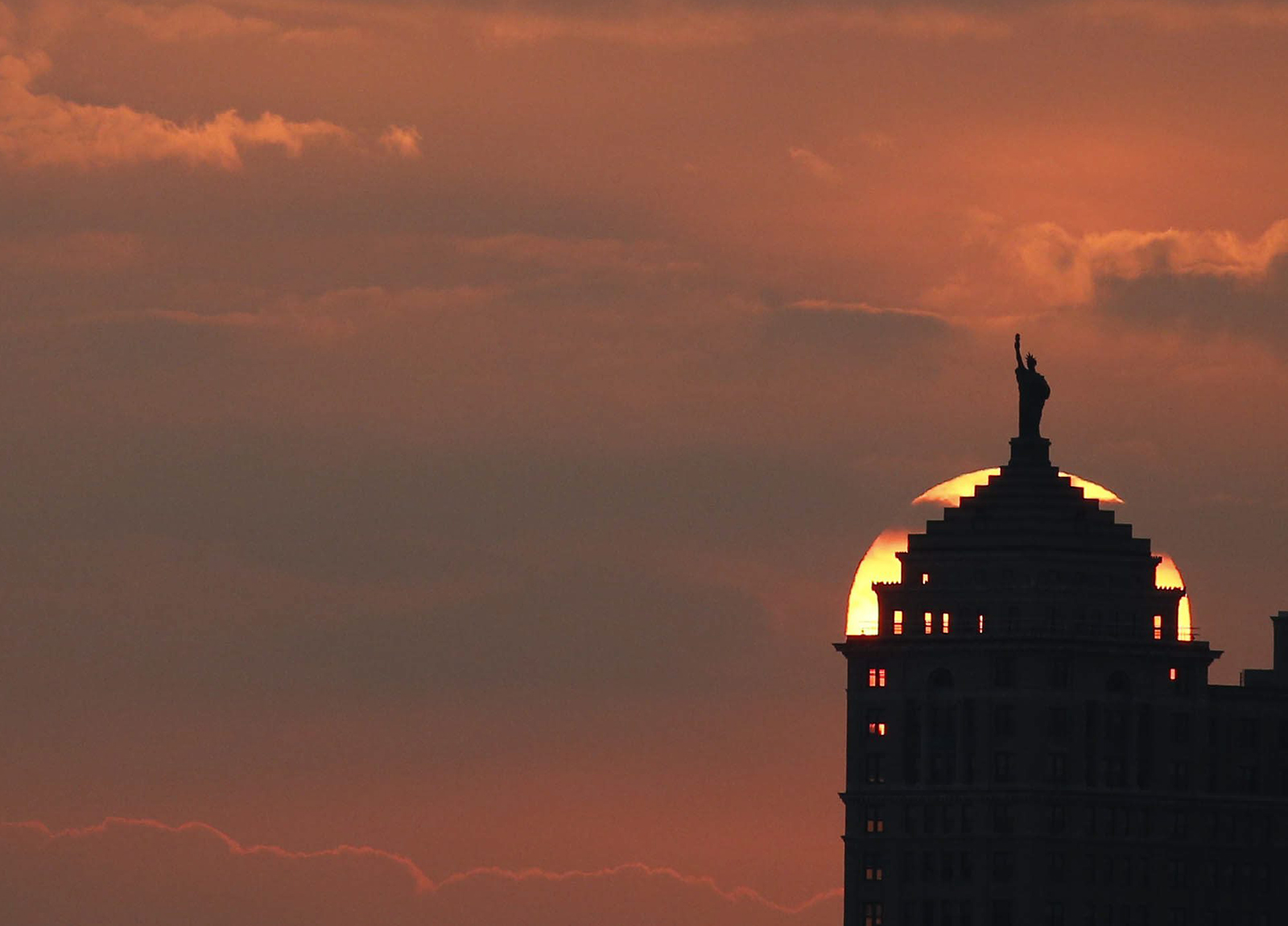 The sun rises behind the Liberty Building in Buffalo, N.Y., Wednesday, July 6, 2016.  (Photo by Derek Gee)