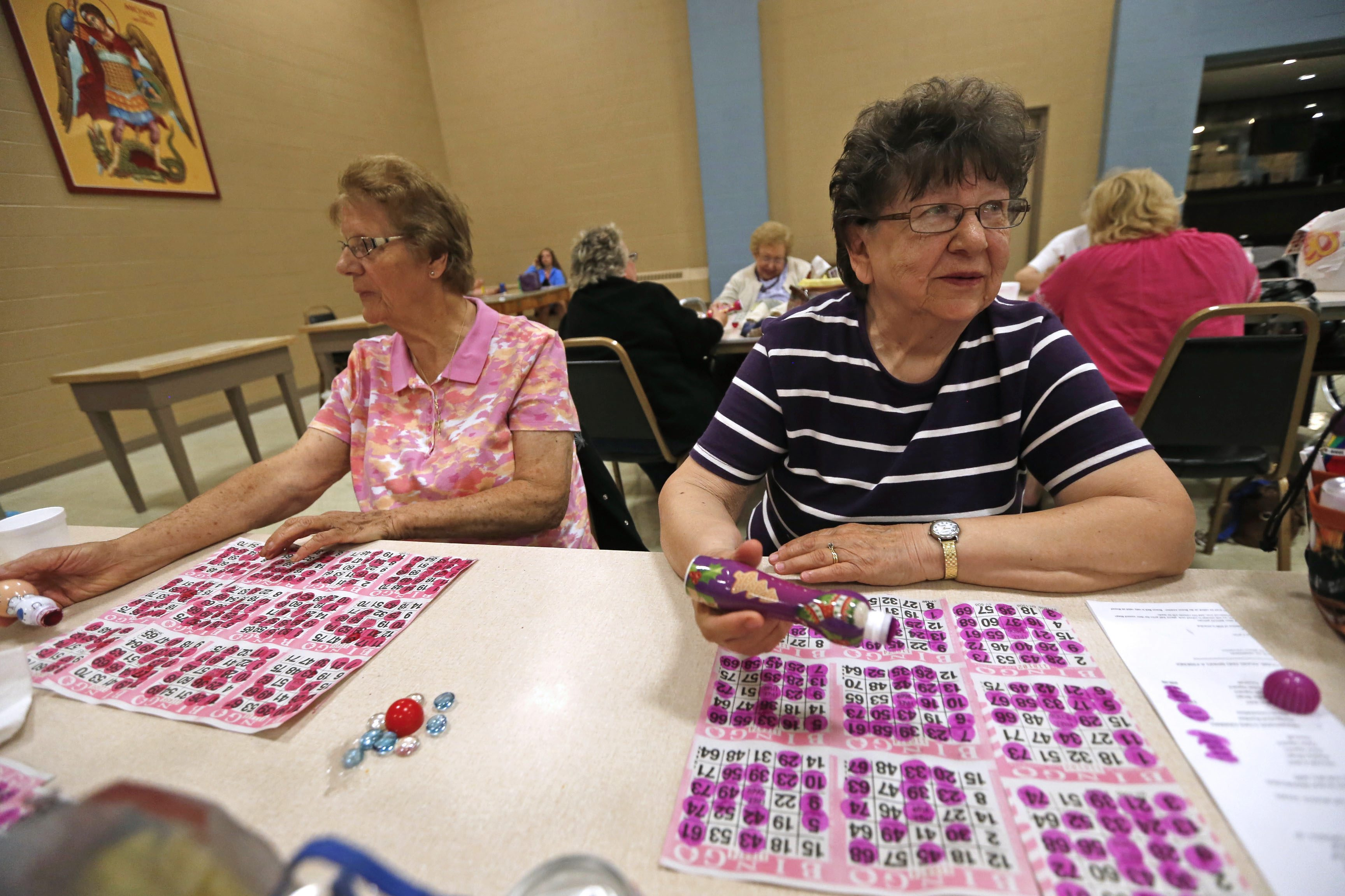 Audrey Dreczka, right, who raised all of her children across the street from the church, uses an ink stamp bottle to mark her cards on Wednesday night BINGO event at the Queen of Angels Parish Community Center on Electric Avenue near Warsaw Street. The community center, which is ground zero for this poverty census study has been a gathering place for decades. (Robert Kirkham/Buffalo News)