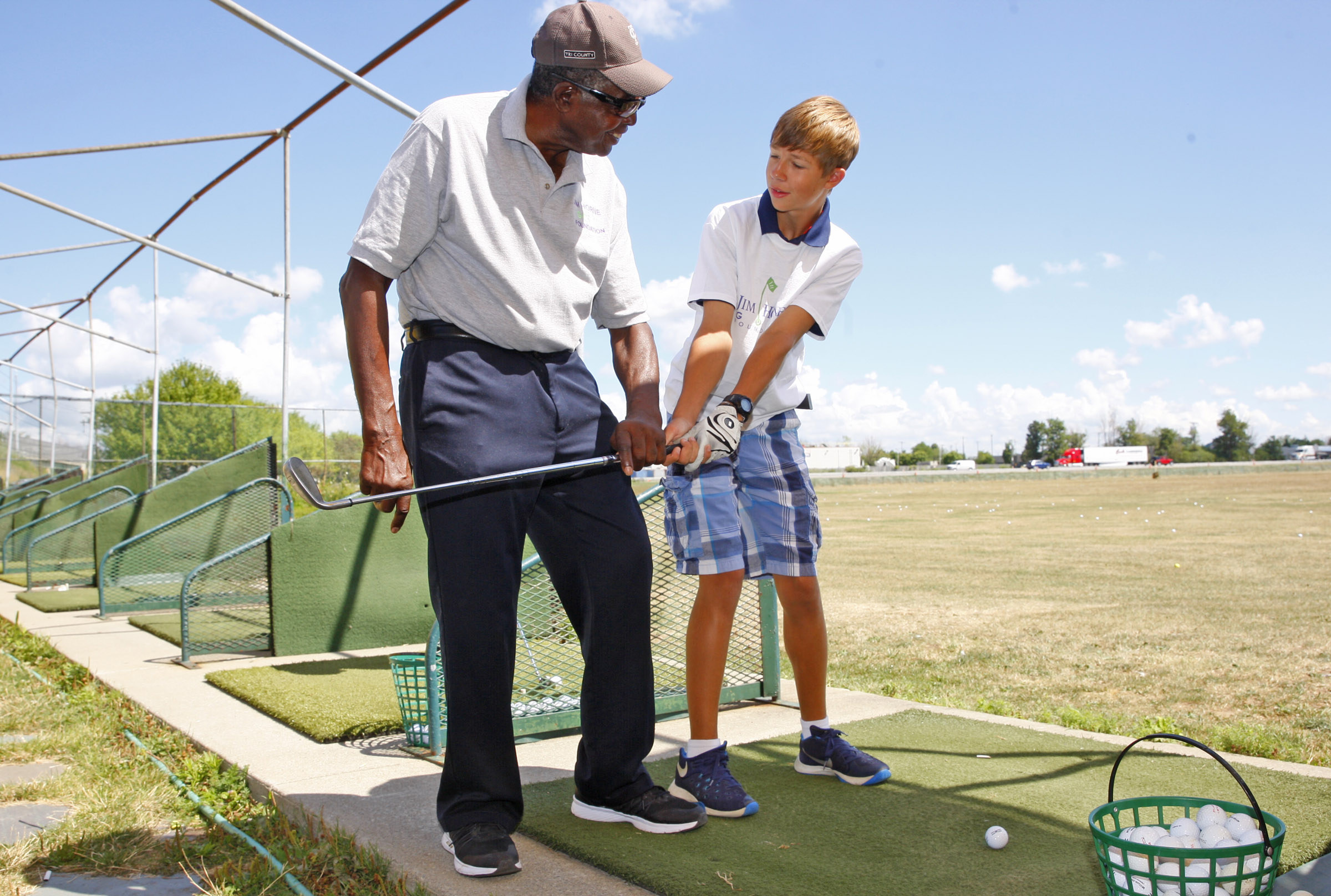 Jim Horne is an 84-year-old former UB basketball player and Harlem Globetrotter gives free golf lessons to Dawson Miller at the Airport driving range on Wednesday, Aug. 3, 2016. (Harry Scull Jr./Buffalo News)