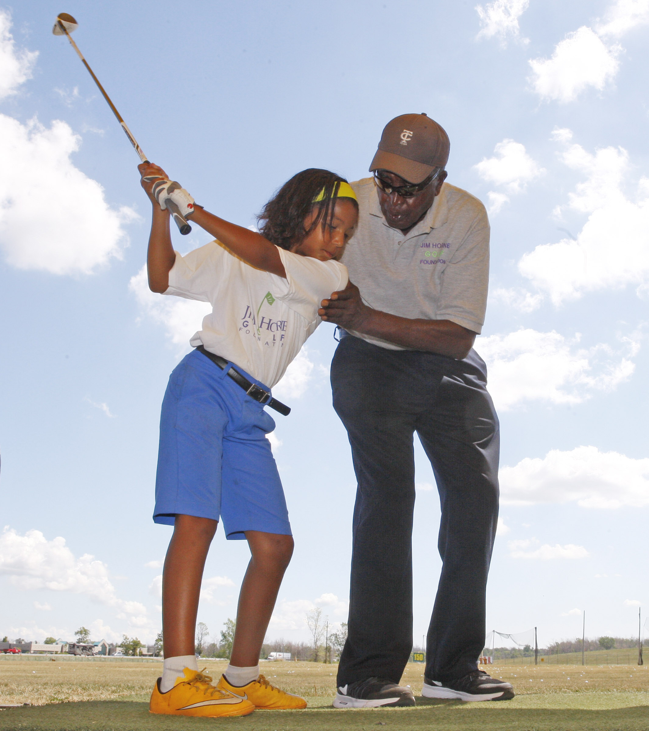 Jim Horne is an 84-year-old former UB basketball player and Harlem Globetrotter gives free golf lessons to Sierra Warren at the Airport driving range on Wednesday, Aug. 3, 2016. (Harry Scull Jr./Buffalo News)