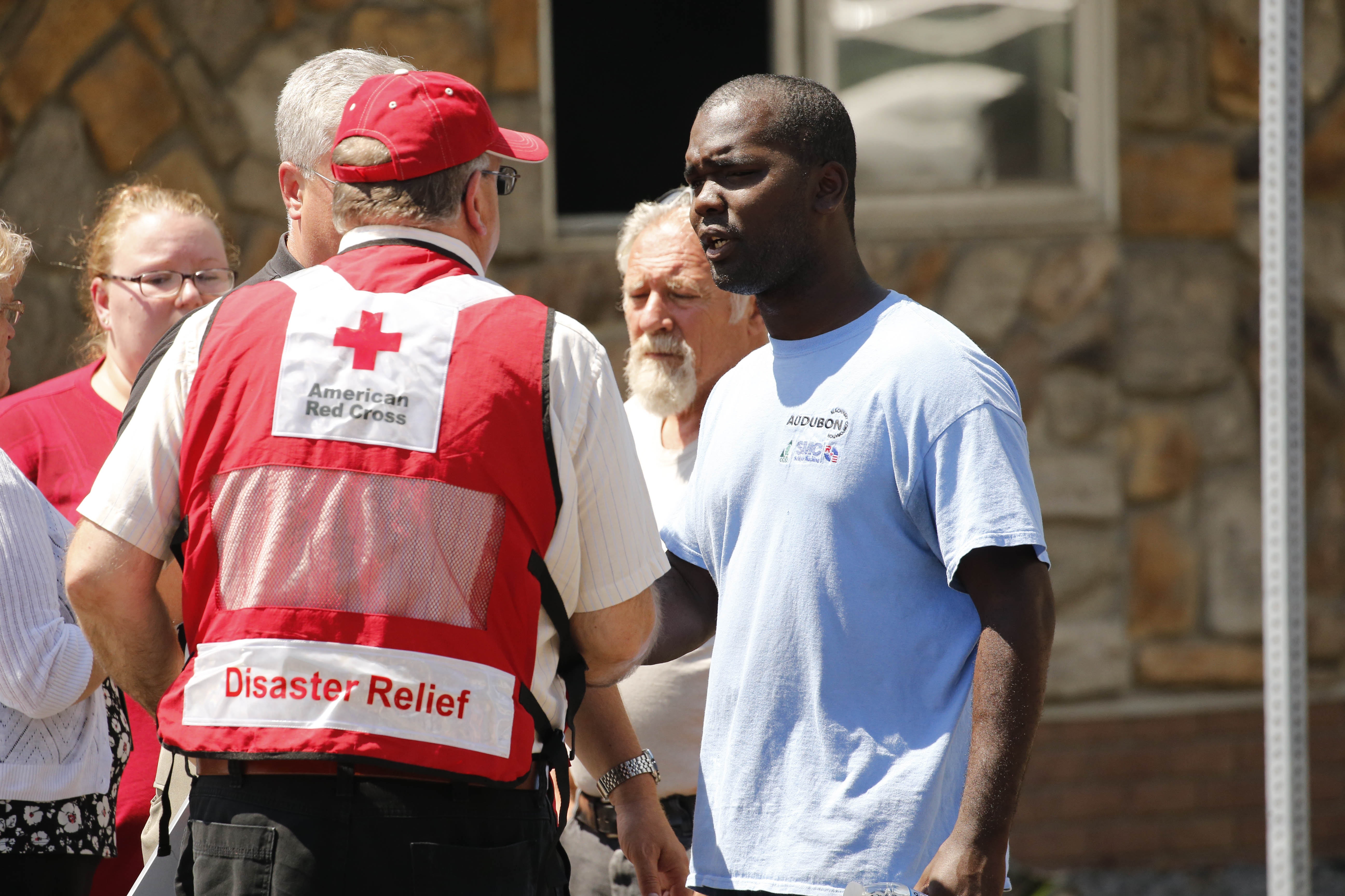 Kenneth Walker talks to a caseworker from the American Red Cross as North Tonawanda police and fire officials investigate the scene of a fire that occurred in his home Wednesday. (Derek Gee/Buffalo News)