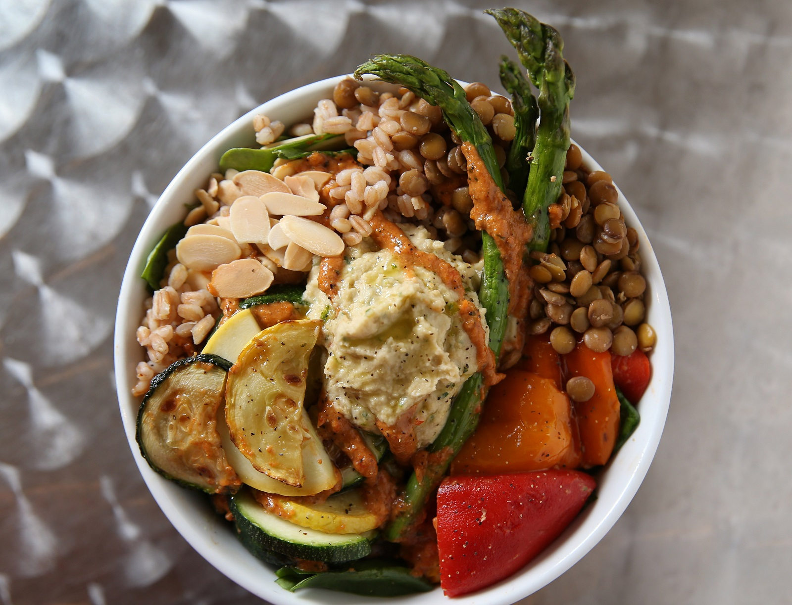 Organic 3 Cafe's grain bowl with grilled summer veggies.  It has organic spinach, organic faro, organic green lentils, locally grown summer squash and zucchini, roasted sweet peppers, asparagus, house-made hummus, toasted almonds, sundried tomato and basil pesto. (Sharon Cantillon/Buffalo News)