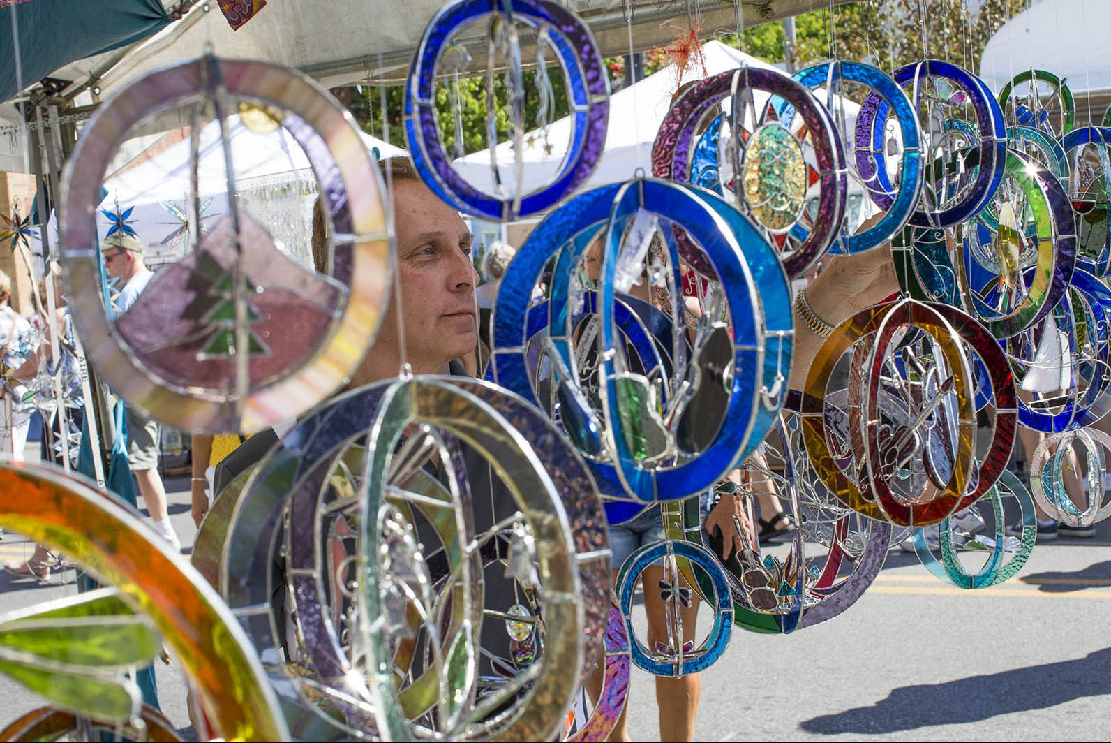 Kevin Schenk of Cheektowaga examines glass art from Katie Knopp of Clyde, North Carolina at the Elmwood Avenue Festival for the Arts, Saturday, Aug. 27, 2016. (Derek Gee/Buffalo News)