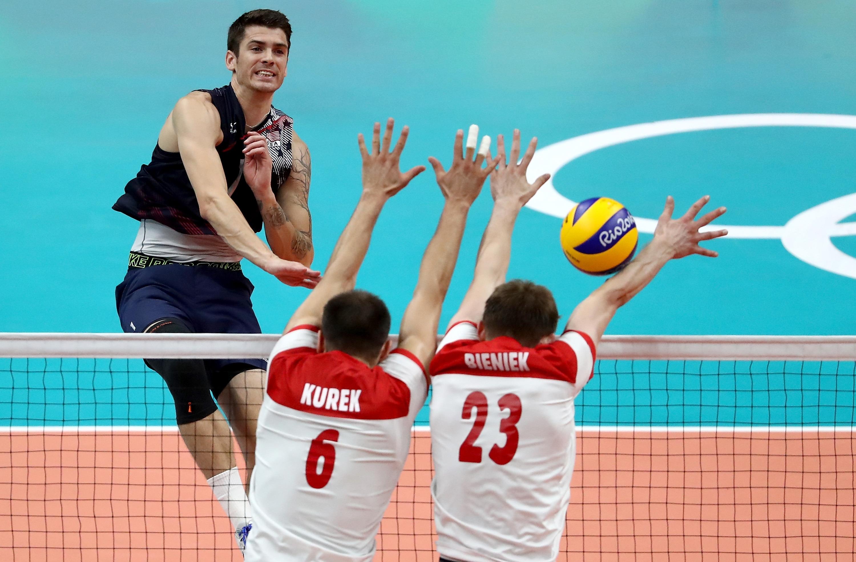 Matt Anderson of United States spikes past Bartosz Kurek and Mateusz Bieniek of Poland in the men's quarterfinal volleyball match on Wednesday.