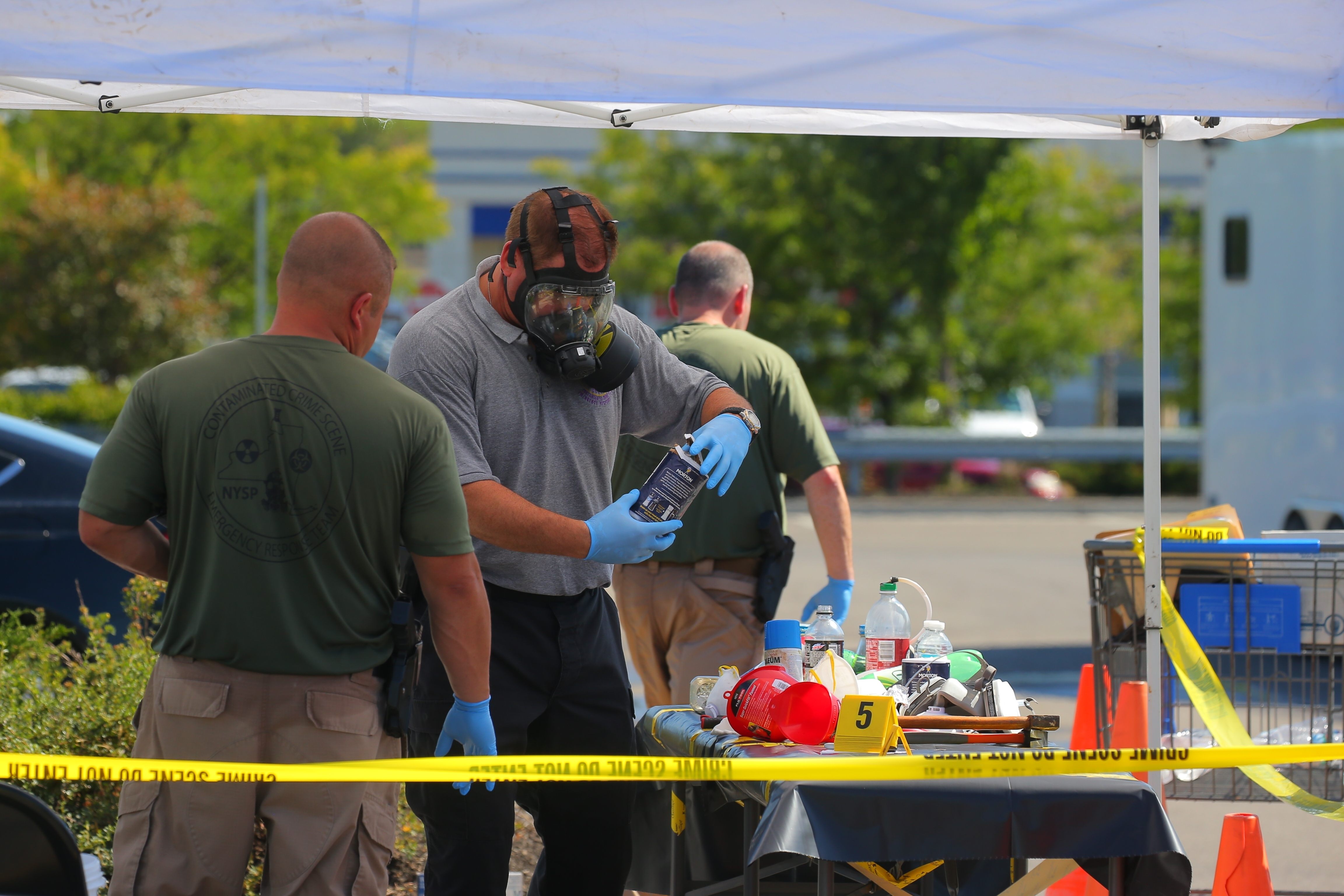 A police official inspects items collected from an active underground meth lab that was discovered by Amherst police down the storm sewer of the Walmart parking lot on Sheridan Drive in Amherst. (John Hickey/Buffalo News)