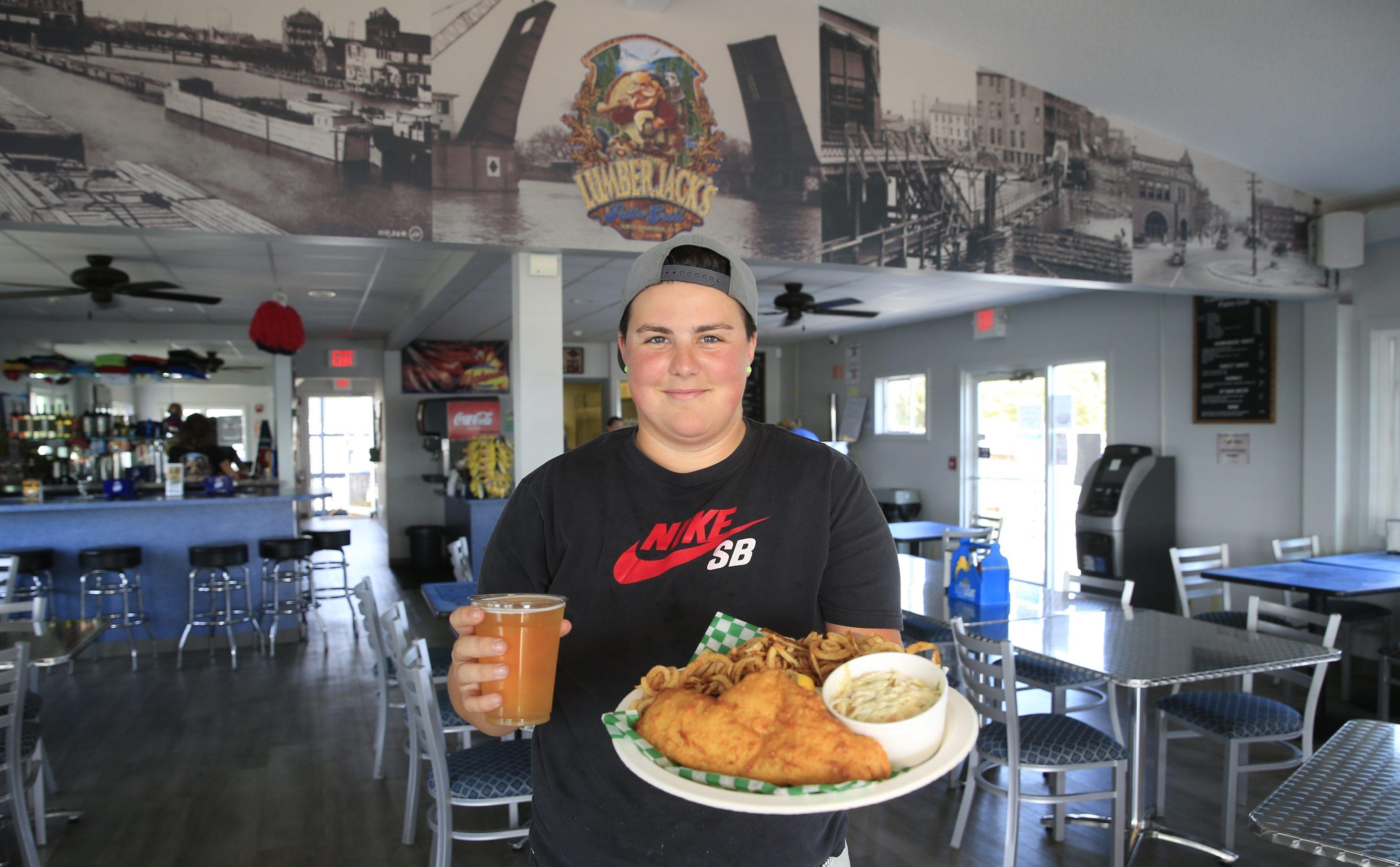 Shaina Bunker holds the everyday fish fry and a draft beer at Lumberjack's in North Tonawanda. (Harry Scull Jr./Buffalo News)