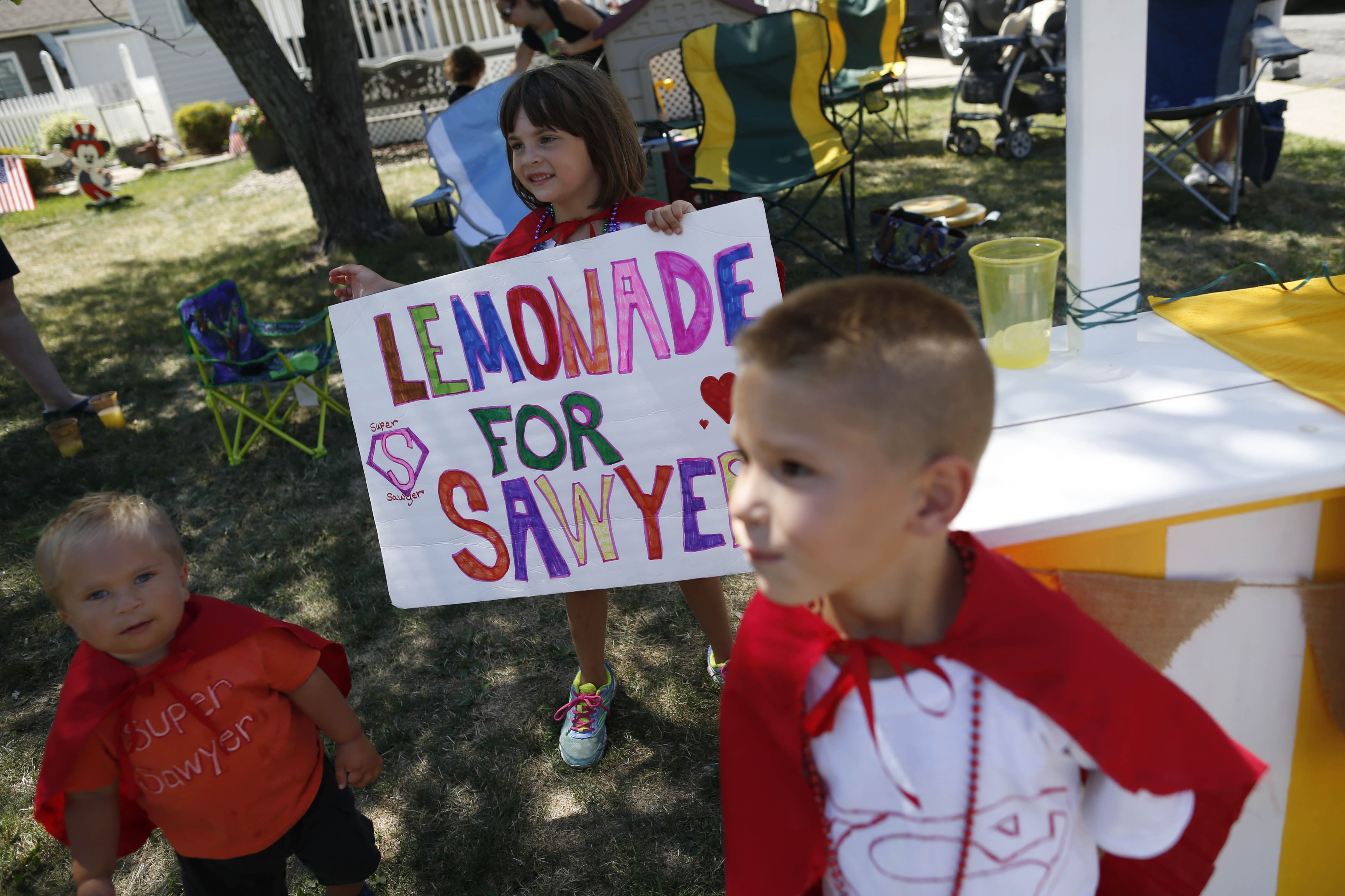 From left, Jace Schunk, 3, Disney Schunk, and Johnathan Dearing, both age 6, run a lemonade stand to raise money for Sawyer Perkins, a family friend with brain cancer, outside their home in West Seneca, Thursday, Aug. 4, 2016.   (Derek Gee/Buffalo News)