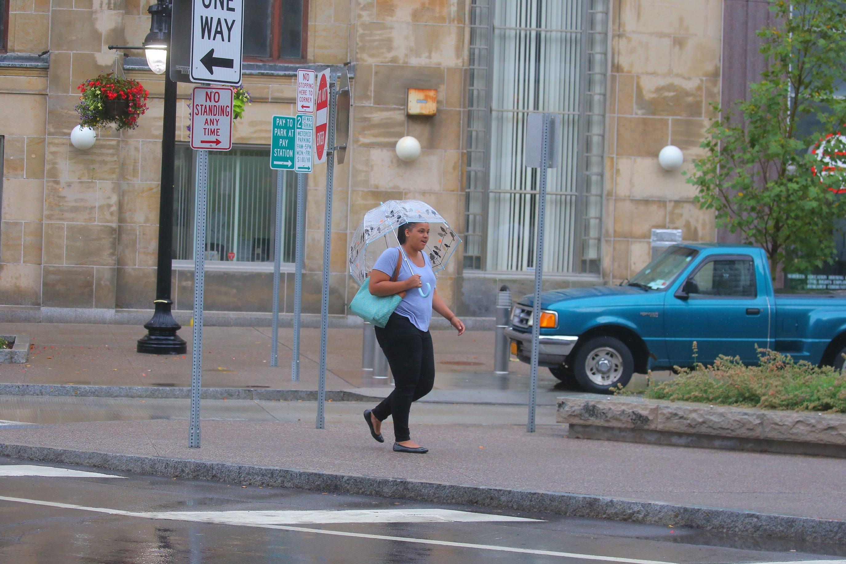 Tavi Cardone heads out for a coffee on Huron Street in a light rain in Buffalo. (John Hickey/Buffalo News)