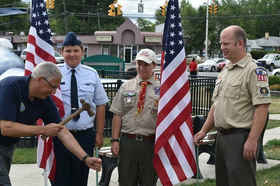 From left, Bob Pecoraro, a Healing Field program chairman, hammers rebar in the ground to hold up a Healing Field flag at Gratwick Riverside Park as Daniel Lee, Jared Sokolik and Ben Costo watch.