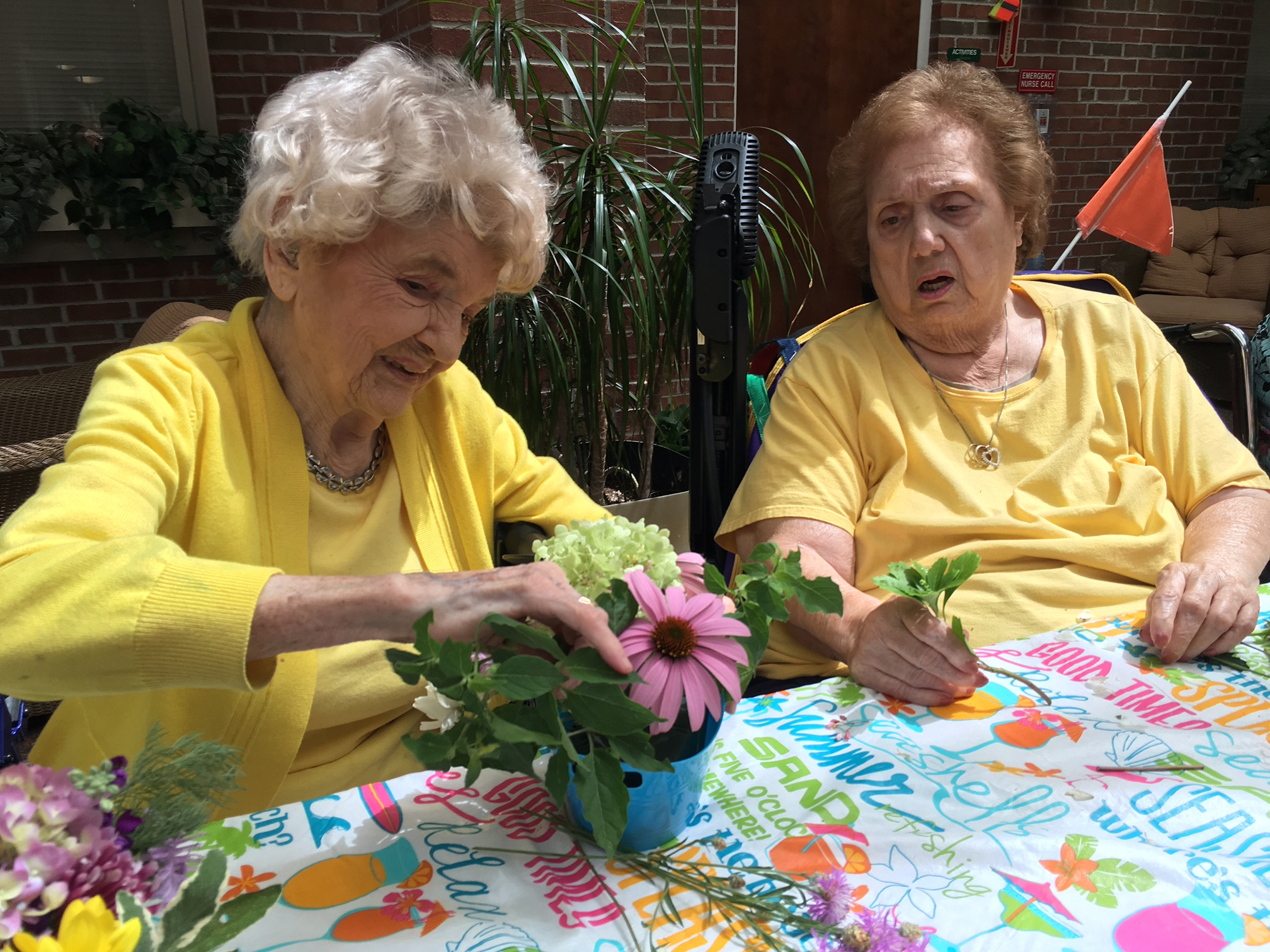 Olive Beutler, left, 101, helps Angie Genovese arrange some flowers.