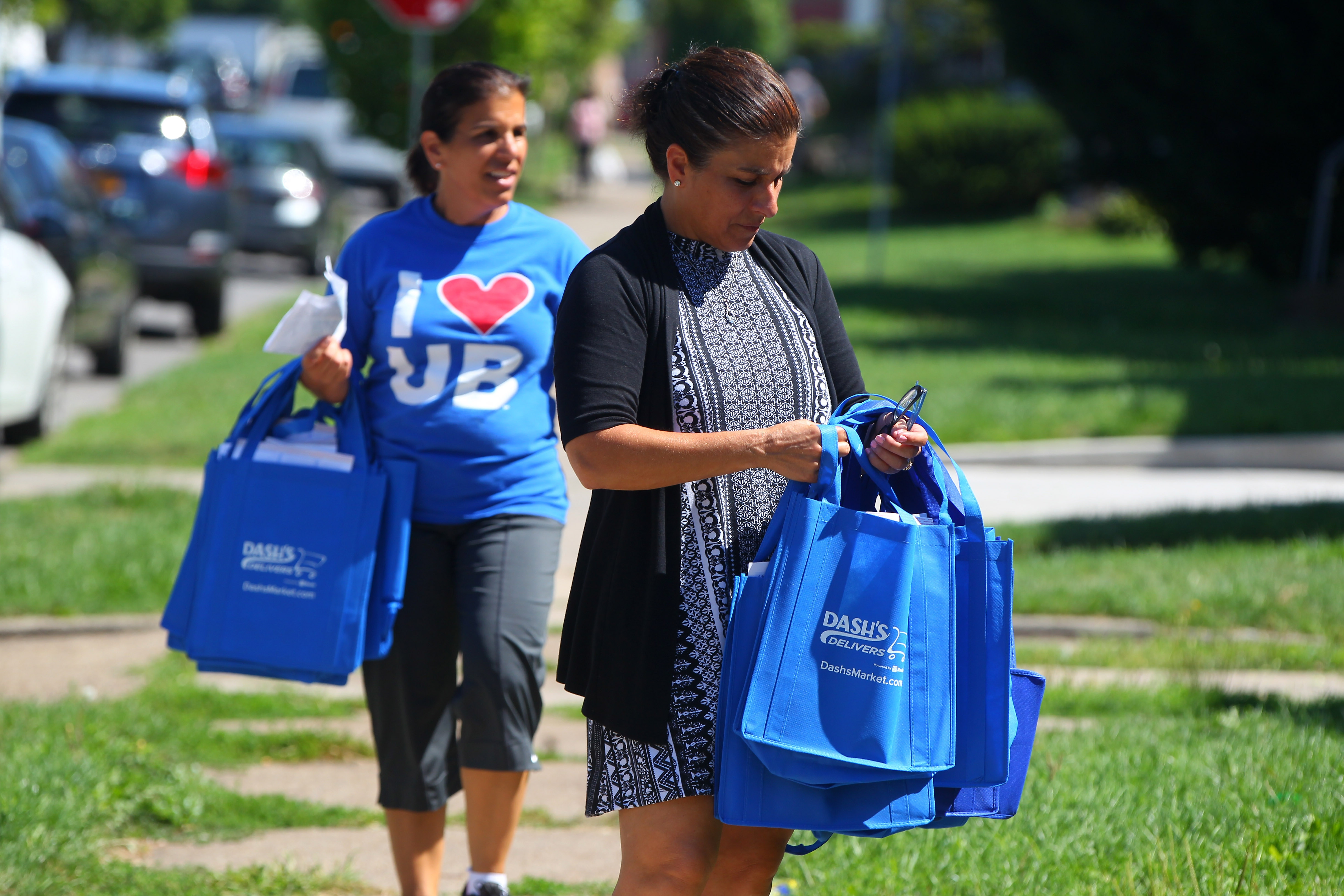 UB staff members Phyllis Floro, left, and Carmella Marinaccio earlier this week passed out informational material to homes in the University District telling students to be good neighbors and telling permanent residents what to do if they have a problem with student neighbors.