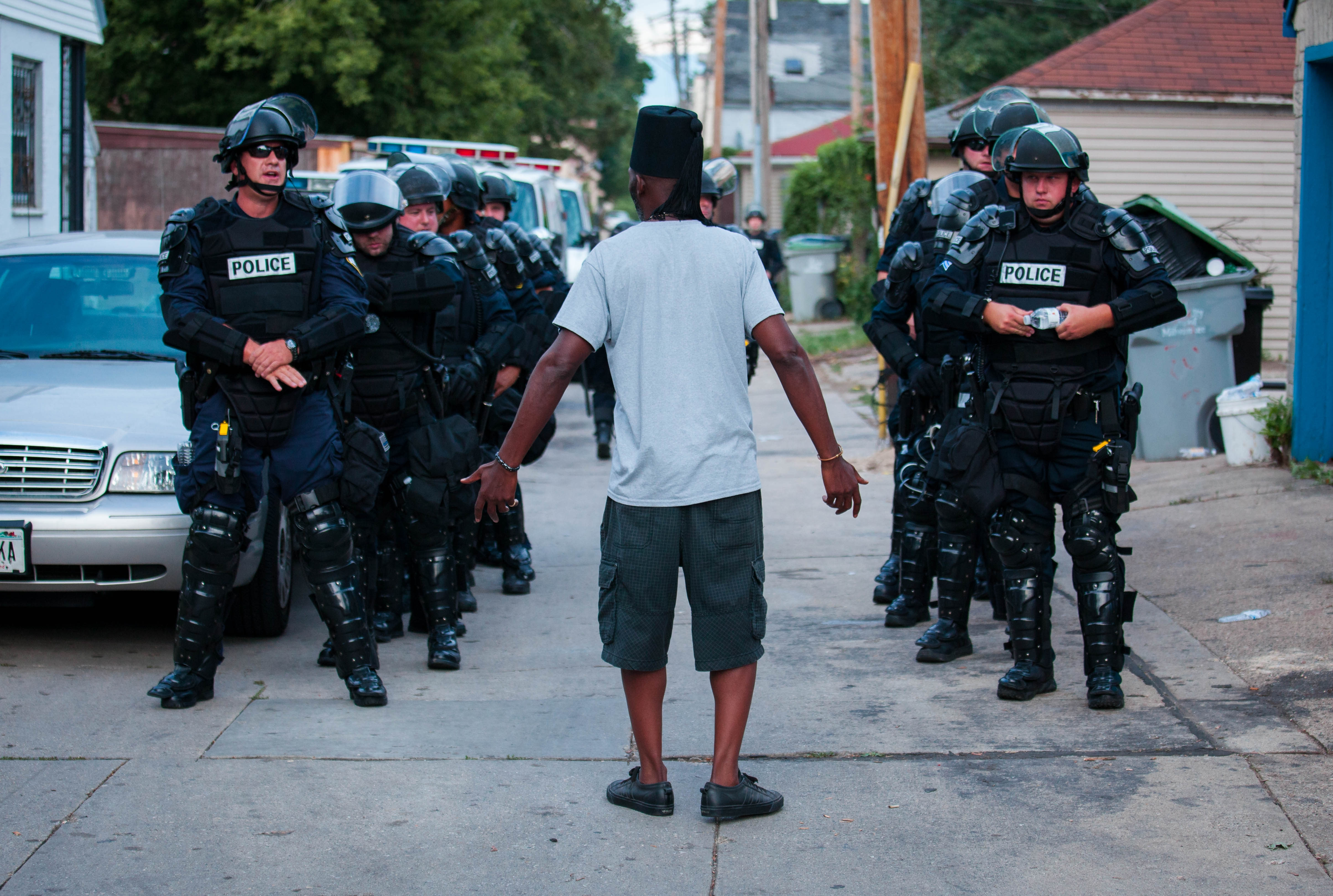 A man talks to police in riot gear as they wait in an alley after a second night of clashes between protesters and police on Aug. 15 in Milwaukee, Wis. Hundreds of angry people confronted police after an officer shot and killed a fleeing armed man. Statistics show there are more than 1,000 police-involved killings in this country every year.