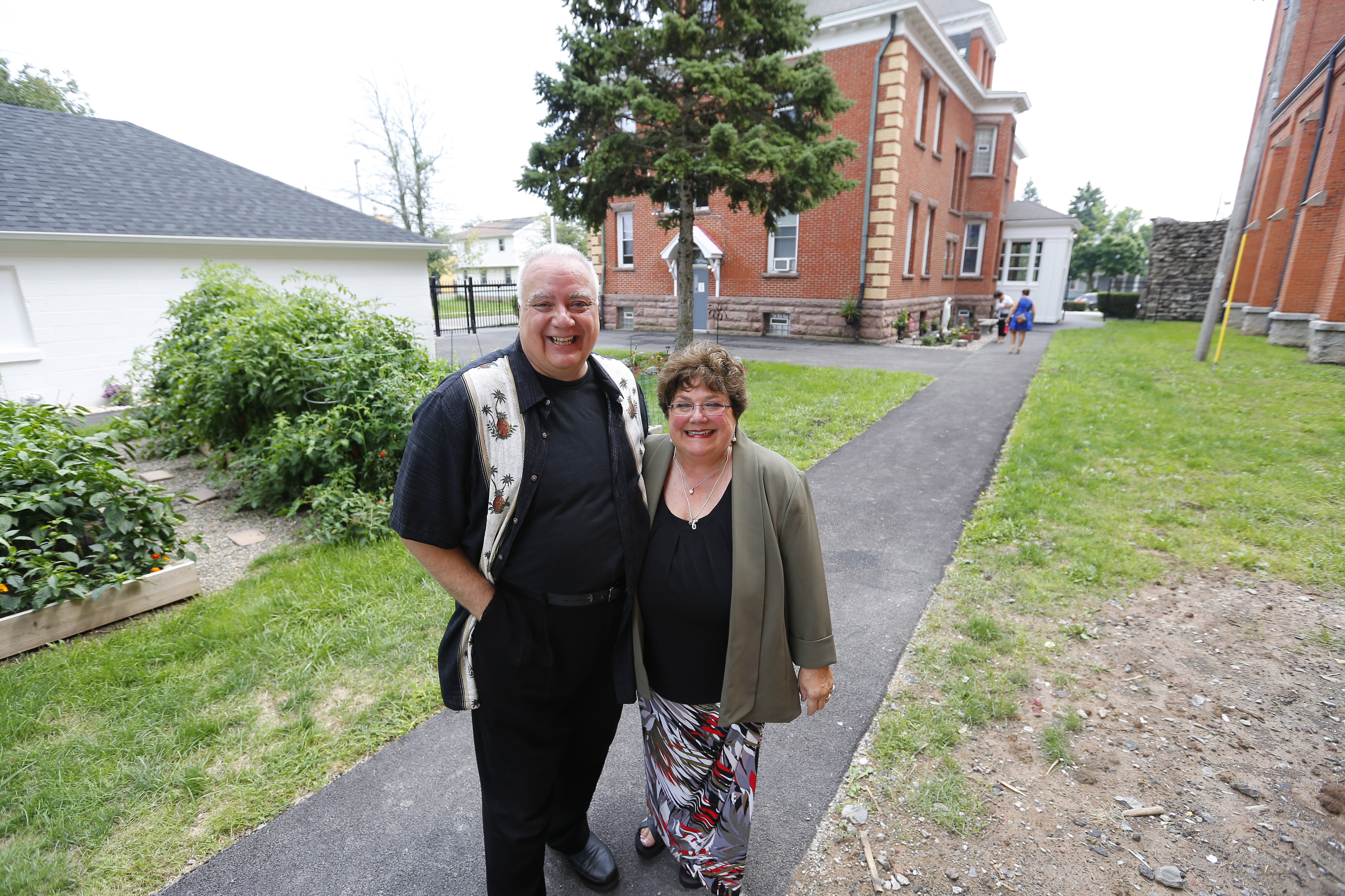 David and Cheryl Calire stand in the garden at the Mother Teresa House -- the former St. Adalbert's rectory -- in Buffalo on Aug. 24.    (Mark Mulville/Buffalo News)
