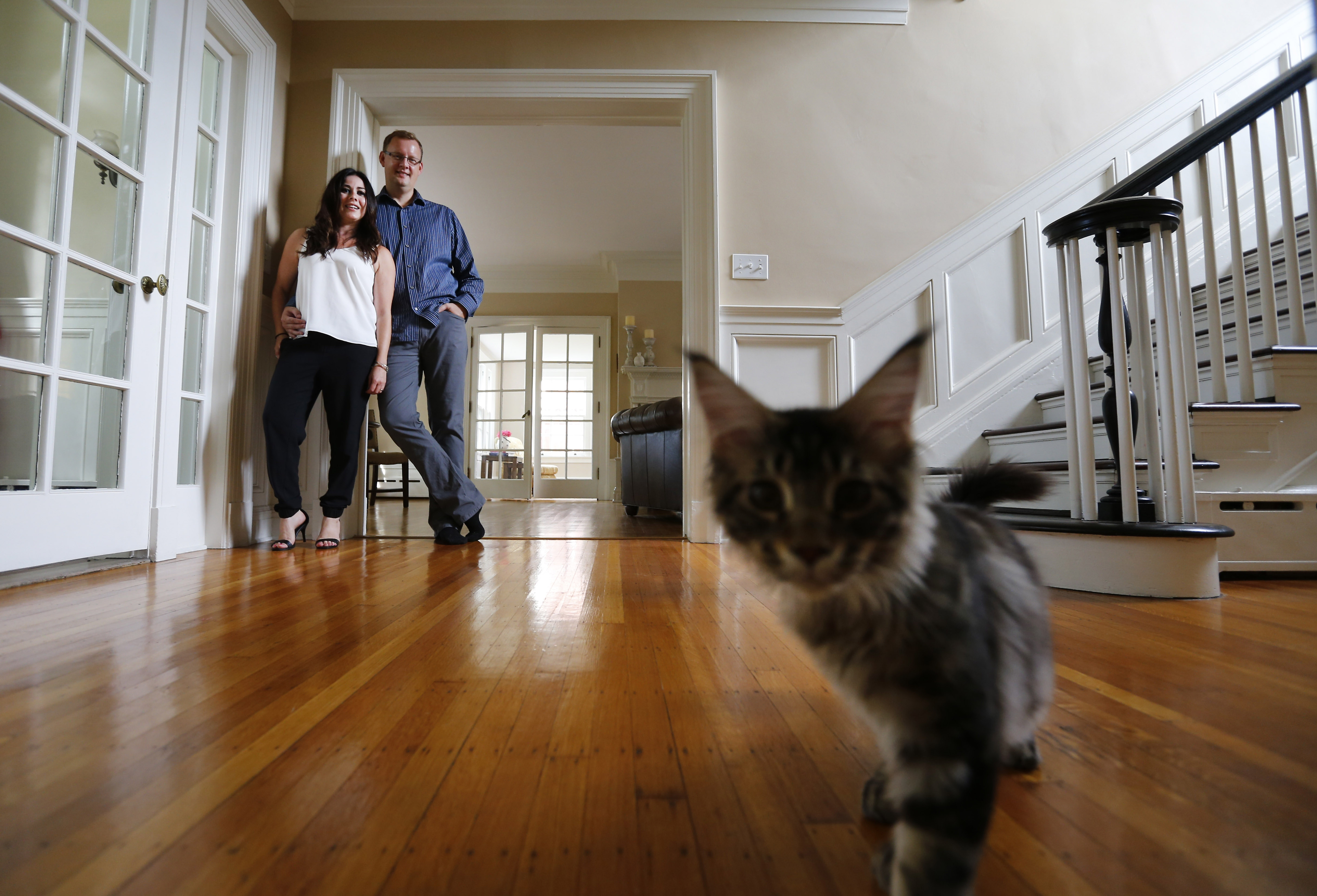 Go with the flow: Dr. Torsten Behrens and Josephine Zagarella pose for a photograph in the foyer of their Central Park home as Loki, one of their three Maine Coons, steals the show. Redecorated spaces include the breakfast room, above left, and one of two guest rooms. The home is on Explore Buffalo's Autumn Tour of Homes on Sept. 23.