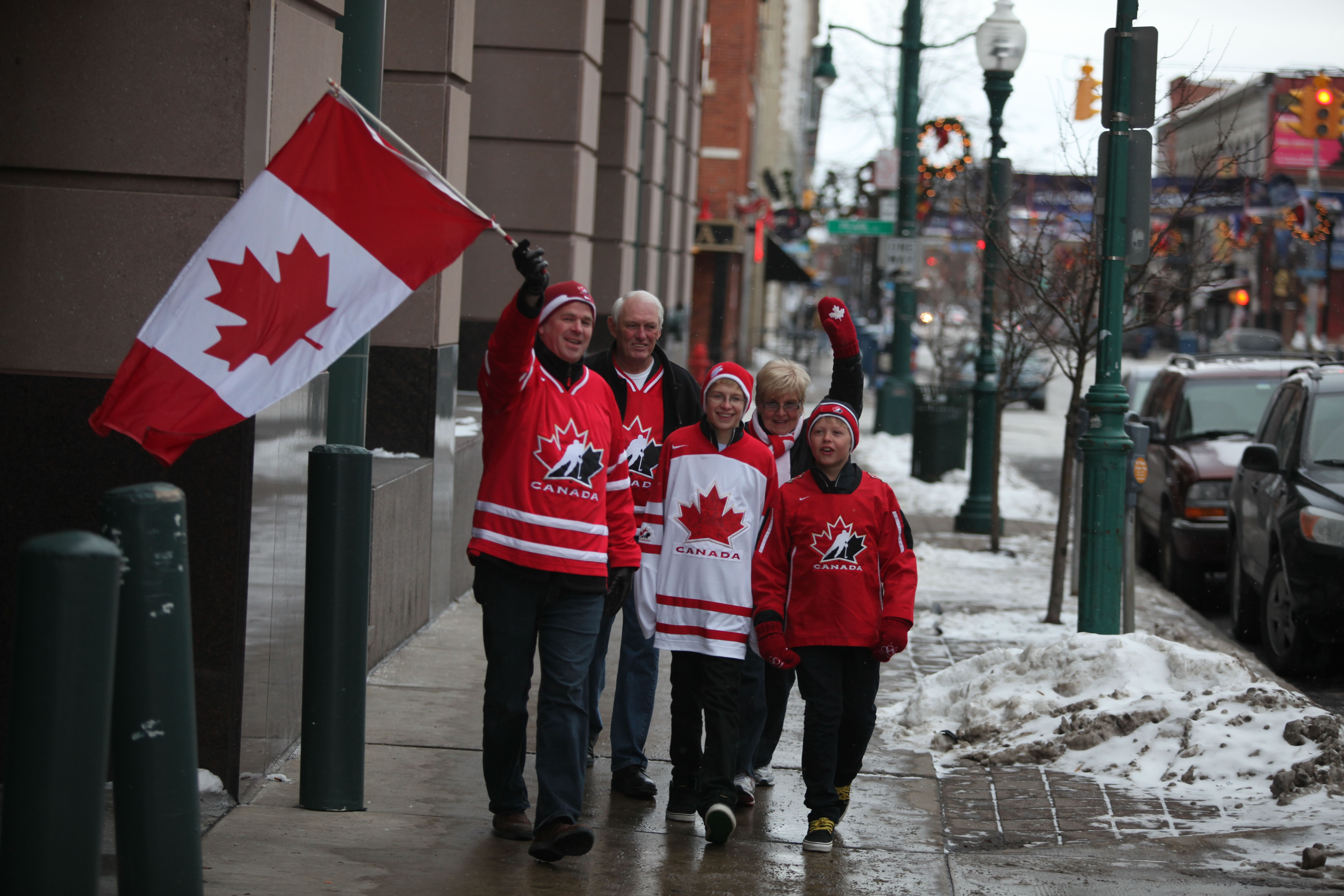 {FOR WATSON/CITYSIDE STORY} Mike Doughty, of Waterloo, Ontario, left, waves a Canadian flag while walking down Chippewa St. in downtown Buffalo with his two sons, Erik, 13, and Zach, 11, and their grandparents, Fred and Carole Freeman, of Calgary, Ontario, Sunday, December 26, 2010. The group was headed to the train station to watch the Junior Hockey Championships at HSBC Arena.  {Photo by Charles Lewis/Buffalo News}