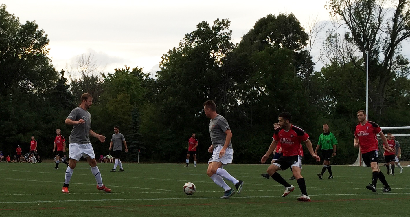 SoHo's Steve Butcher wheels away from pressure as two Sharpshooters defenders watch. (Ben Tsujimoto/Buffalo News)