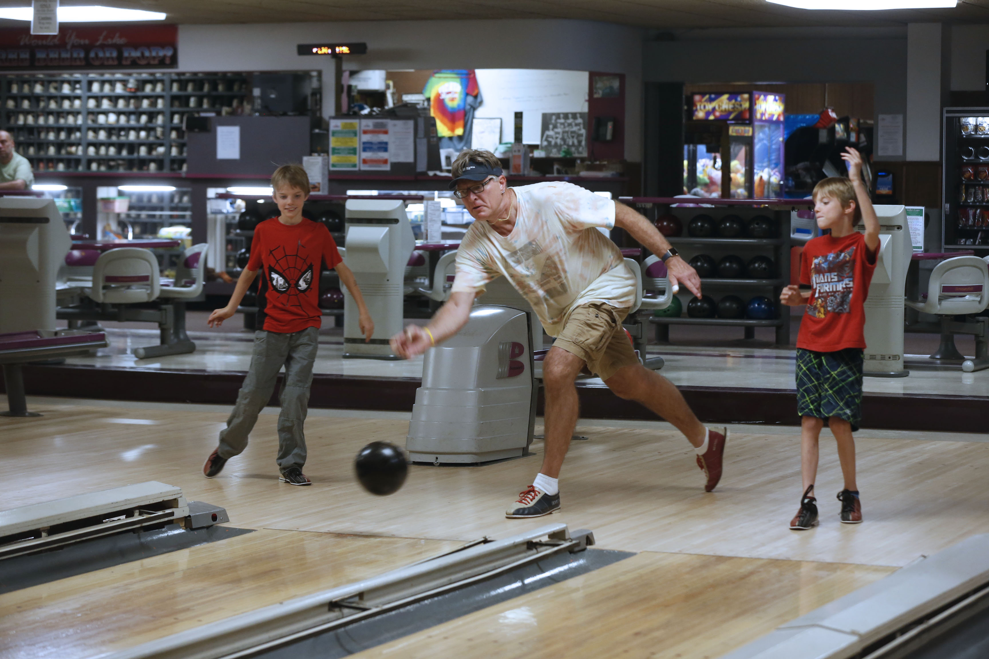 Paul Biddle of Eggertsville and his twin 9-year-old sons, Beau, on left, and Bruno, bowl at Voelker's Lanes in Buffalo on Aug. 8. They ended up being the only customers there that night, which is not unheard of during the summer.  (Robert Kirkham/Buffalo News)
