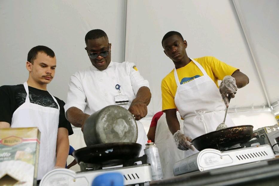 F Bite students Quinn Saunders, left, and Ivan Hunter flank chef Bobby Anderson, at a cooking event at Canalside. (Derek Gee/Buffalo News file photo)
