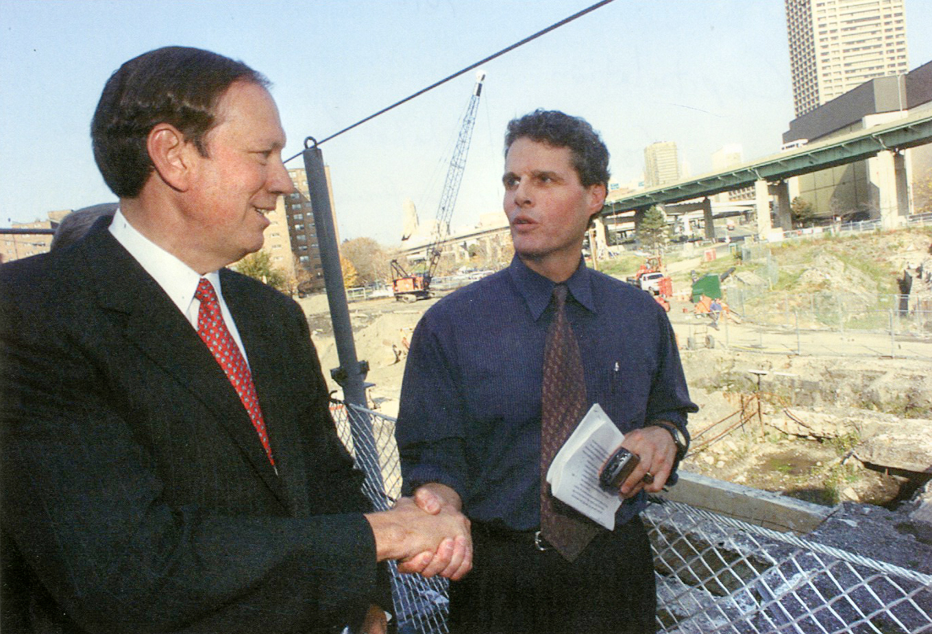 In this Oct. 27, 2000 file photo, Gov. Pataki shakes hands with Donn Esmonde after an Inner Harbor press conference announcing state had reversed course and would excavate and re-water the historic Commercial Slip, now the historic centerpiece of Canalside. Esmonde wrote 16 columns urging the Pataki-controlled state agency to change its plan to leave buried the Slip and surrounding building ruins. (Buffalo News file photo)