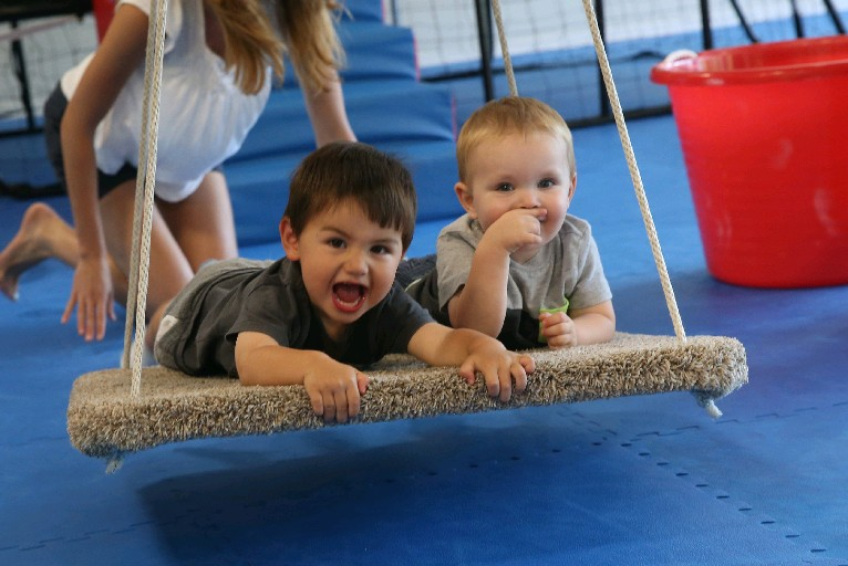 Alex Henry, left, and Nolan Trzesniewski, both 2, enjoy the platform swing on Tuesday at We Rock the Spectrum Buffalo Southtowns.