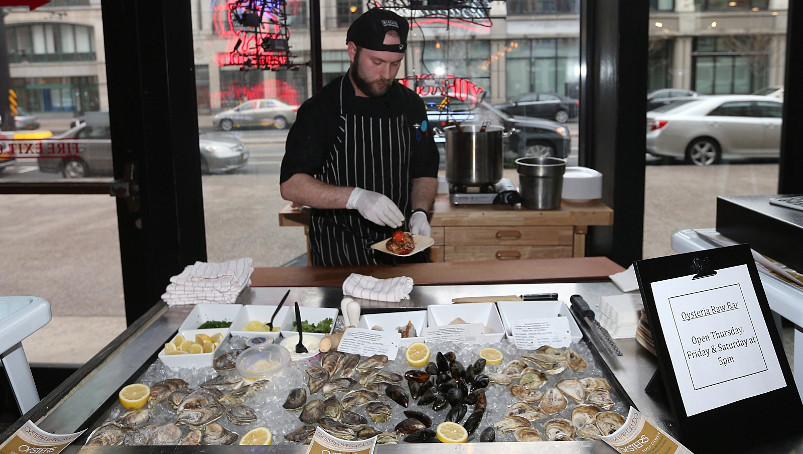 Ken Legnon works with oysters during a previous stint at Oysteria Raw Bar inside EXPO Market. (Sharon Cantillon/Buffalo News)