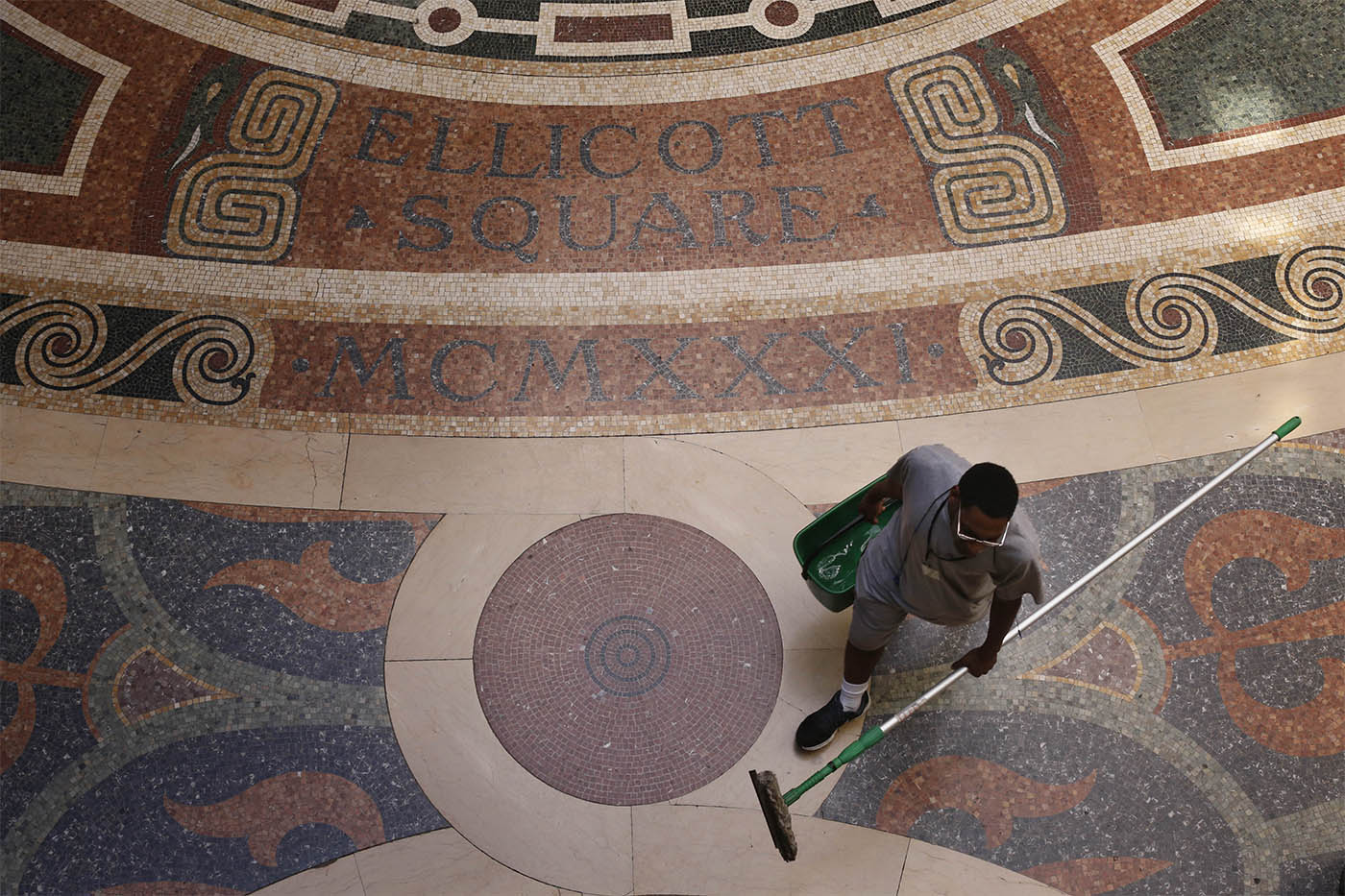 A maintenance man walks past the mosaic tile floor in the lobby of the Ellicott Square Building, Wednesday, Aug. 10, 2016. (Derek Gee/Buffalo News)