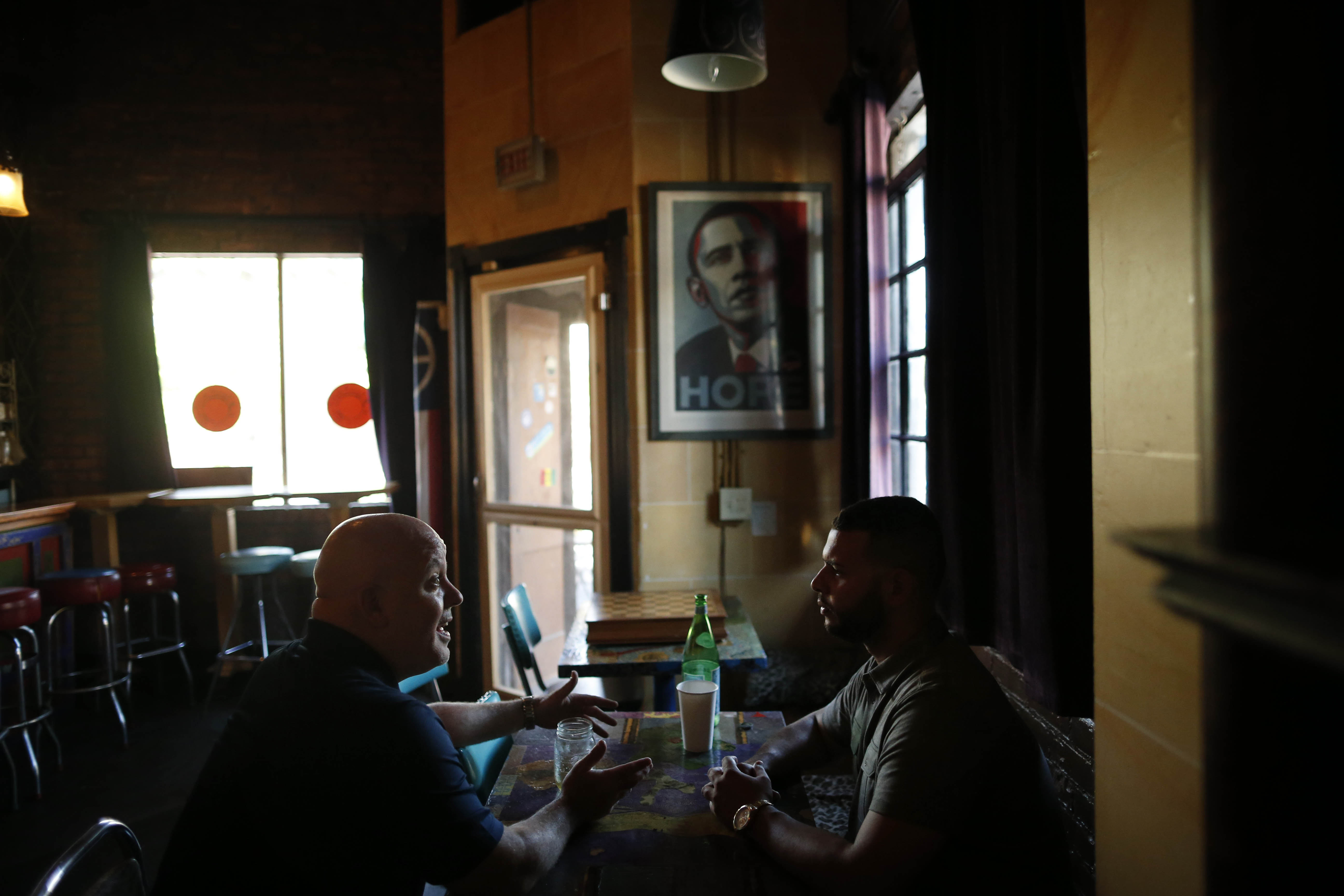 John Starkey, the new principal of Lafayette High School, left, chats with teacher aid Lawrence Ramos during a visit to chat at Sweetness_7 on Grant Street. (Derek Gee/Buffalo News)