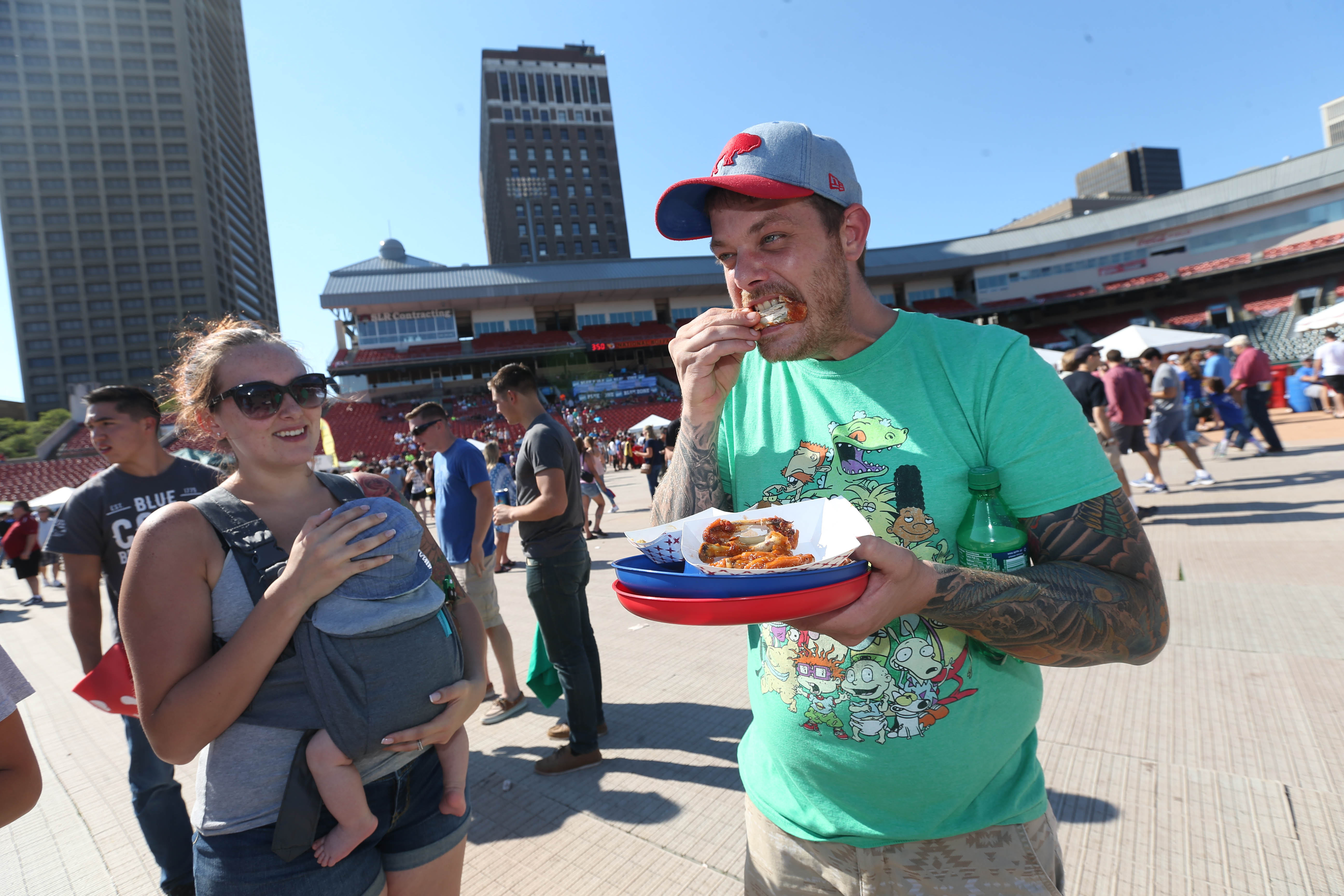 The 15th Annual National Buffalo Wing Festival kicks off, Saturday, Sept. 3, 2016. Rich Straw of South Buffalo munches on some wings as his girlfriend Jessie Hitman, left, holds their son Richard Straw Jr., 6 weeks, probably the youngest attendee at the festival. (Sharon Cantillon/Buffalo News)