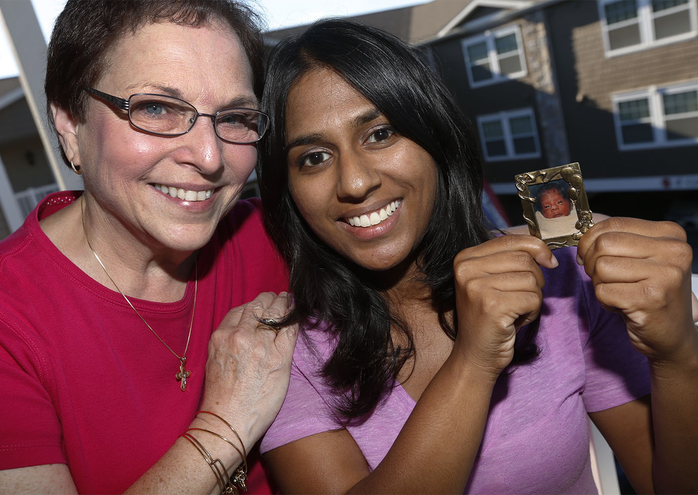 Lynette Grandits and her adopted daughter Rachel, 23, holding a photo of herself as an infant, at her East Amherst apartment on Monday, Aug. 29, 2016. (Robert Kirkham/Buffalo News)