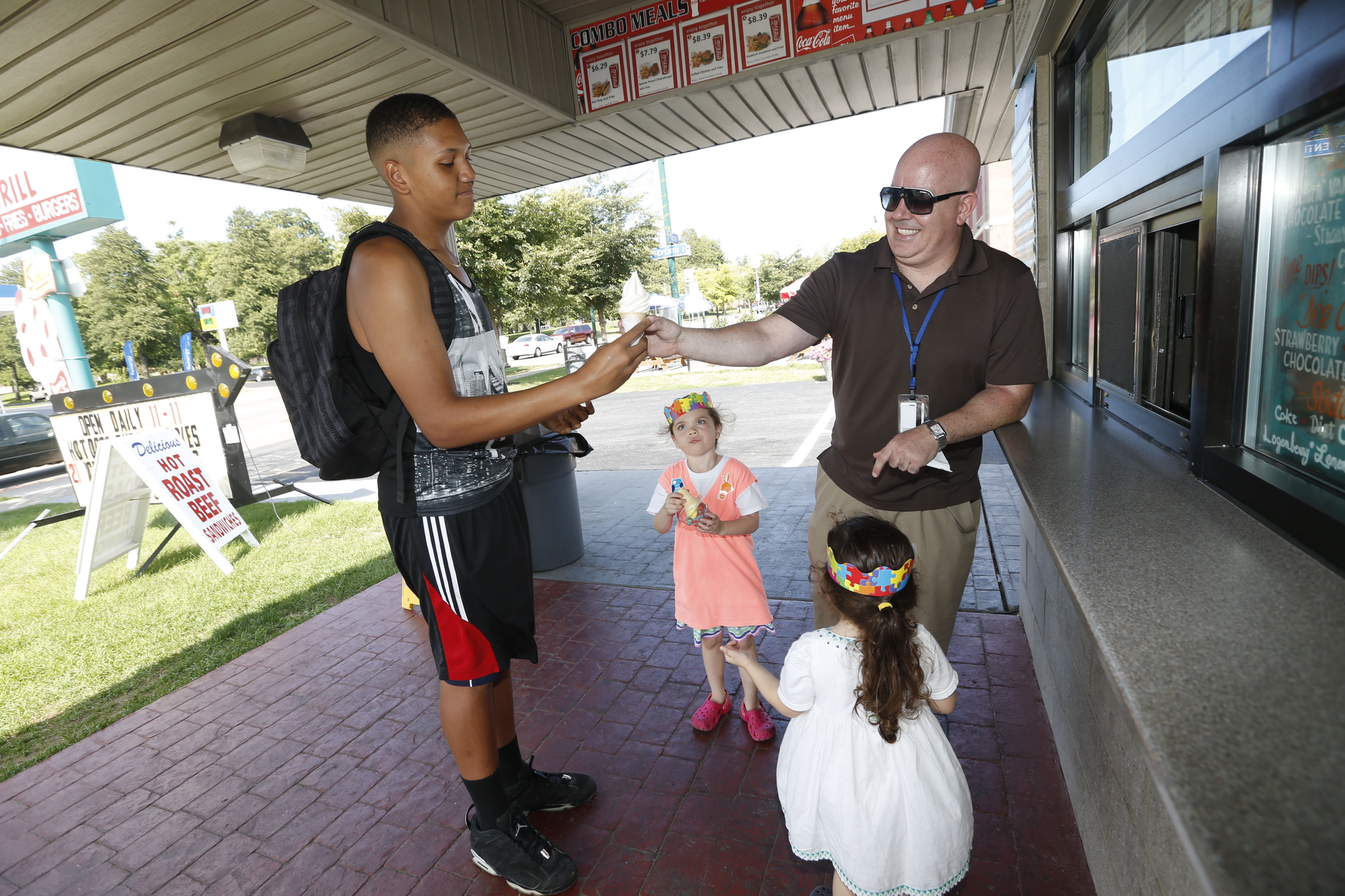 John Starkey, the new principal at Lafayette High School, with his daughters Mia Luz, 3, front, and Marisol, 5, at his side, orders ice cream for John Torres, 17, recently from Puerto Rico, he ran into at a popular West Side ice cream shop at the corner of Porter Avenue and Seventh Street. (Robert Kirkham/Buffalo News)